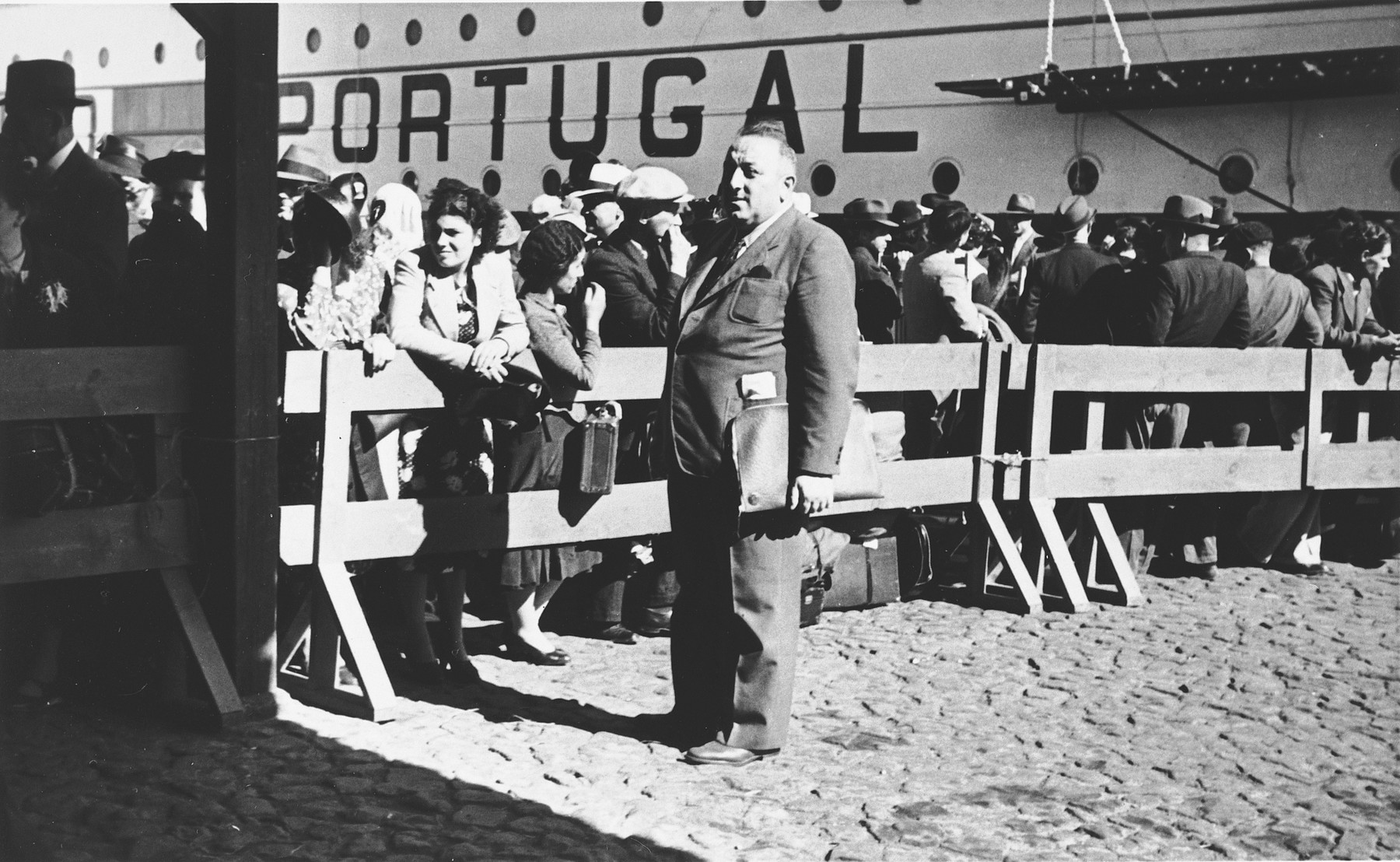 Albert Nussbaum, Director of Transmigration for the American Joint Distribution Committee, poses in the port of Lisbon in front of a wooden fence that cordons off the Jewish refugees who are waiting to board the SS Mouzinho.