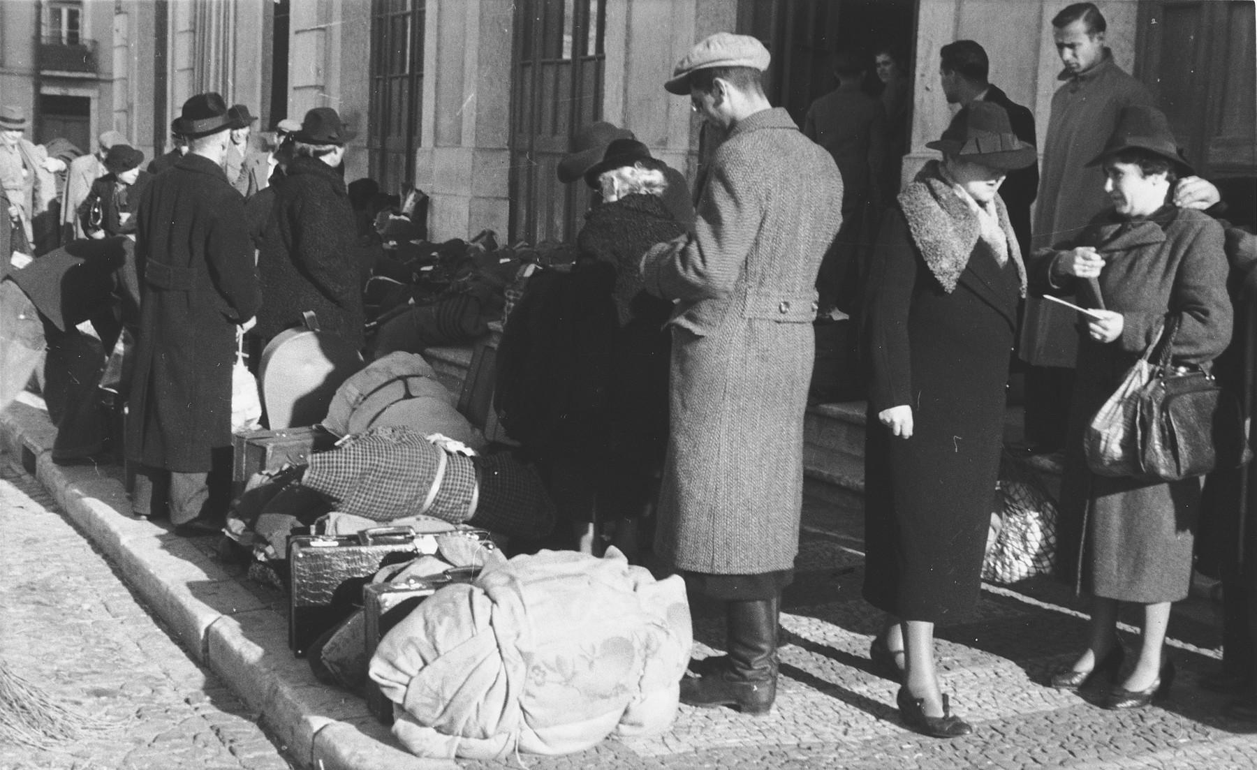A group of Jewish refugees who have just arrived in Lisbon wait with their luggage in front of the St. Appolonia train station.