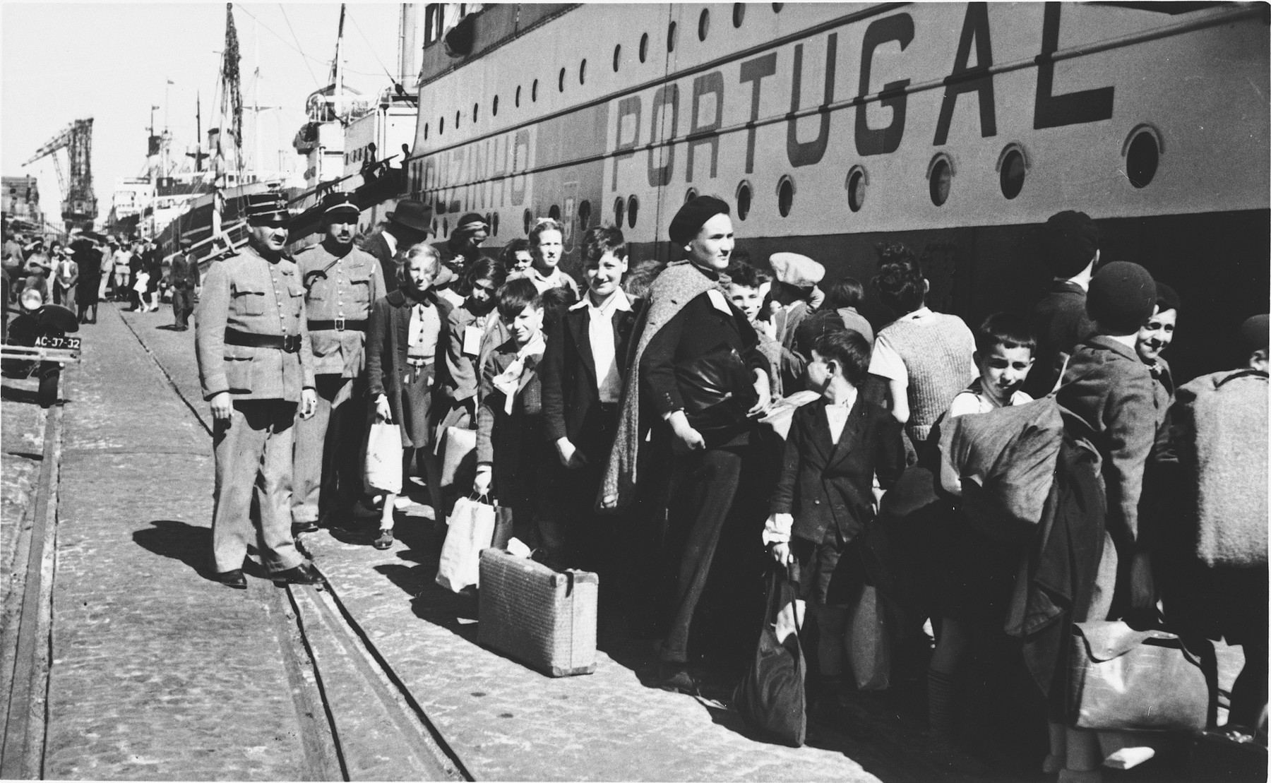Two uniformed Portuguese policemen stand on the pier in the port of Lisbon as a group of Jewish refugee children wait in line to board the SS Mouzinho.  The young boy just to the right of center in the image, looking back over his right shoulder, is Herman Rosenfeld, born 27 April 1933 in Adelheim, Germany.  The young blonde girl standing next to the two police officers is wearing tag #25, can be identified as Lilian Warschawski (or Warszawski), born 20 April 1930 in Belgium.