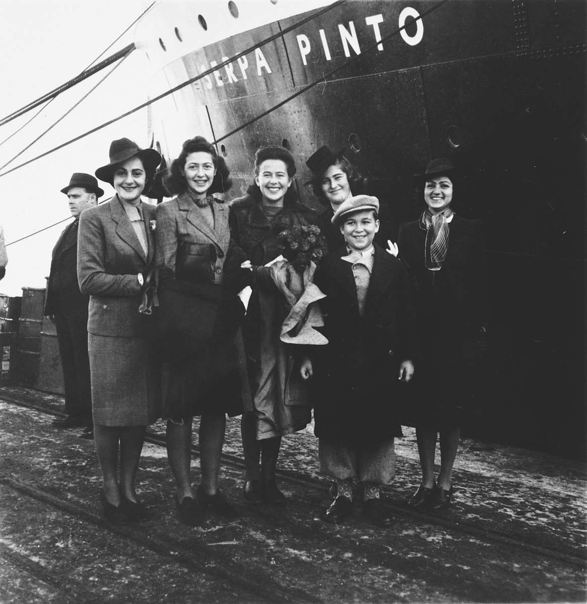 A group of Jewish refugees pose on the pier in the port of Lisbon before boarding the SS Serpa Pinto.   Among those pictured is Madeleine Hecht Feher, center holding a bouquet of flowers, surrounded by her co-workers from the American Joint Distribtuion Committee.  They came to wish her farewell before embarking.  Also pictured is her brother, Thomas Hecht, the young boy in front.   Pictured on the far left is Lolita Goldstein, a JDC worker.