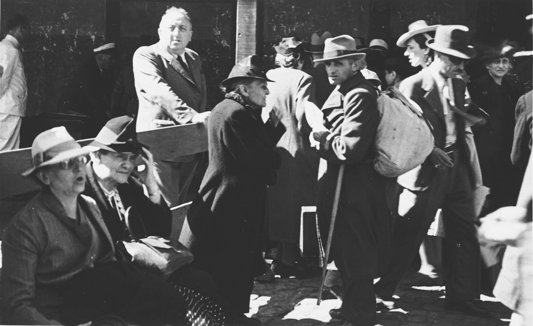 Albert Nussbaum, Director of Transmigration for the American Joint Distribution Committee, observes the scene at the port of Lisbon where Jewish refugees wait to board the SS Mouzinho.