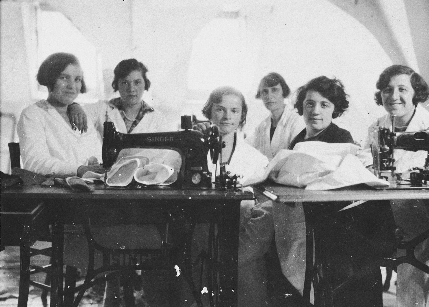 A group of young female employees pose at their sewing tables in the Palais d'Habillement clothing company in Luxembourg.  Among those pictured are the owner's twin sisters, Magdalena and Margaretha Nussbaum (probably first and second on the left).