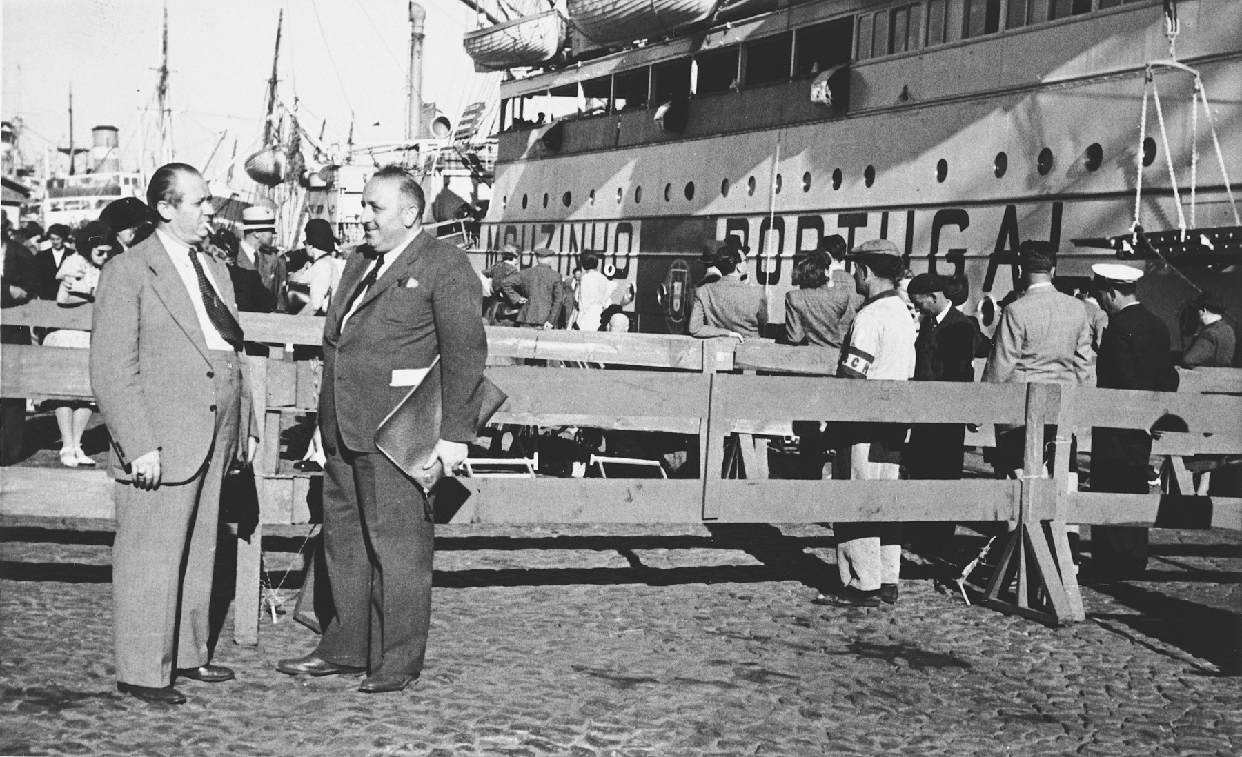 Albert Nussbaum (center right), Director of Transmigration for the American Joint Distribution Commitee converses with a colleague on the pier in the port of Lisbon before the departure of the SS Mouzinho.