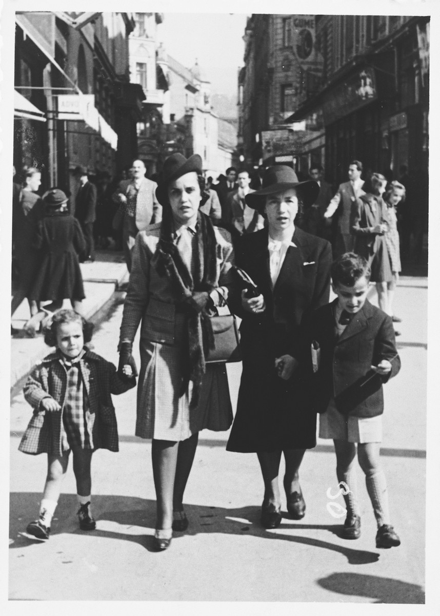 A Jewish family walks along a commercial street in Sarajevo.  Pictured is Mimi Altarac with her children, Jasa and Lela, and a female friend or relative.