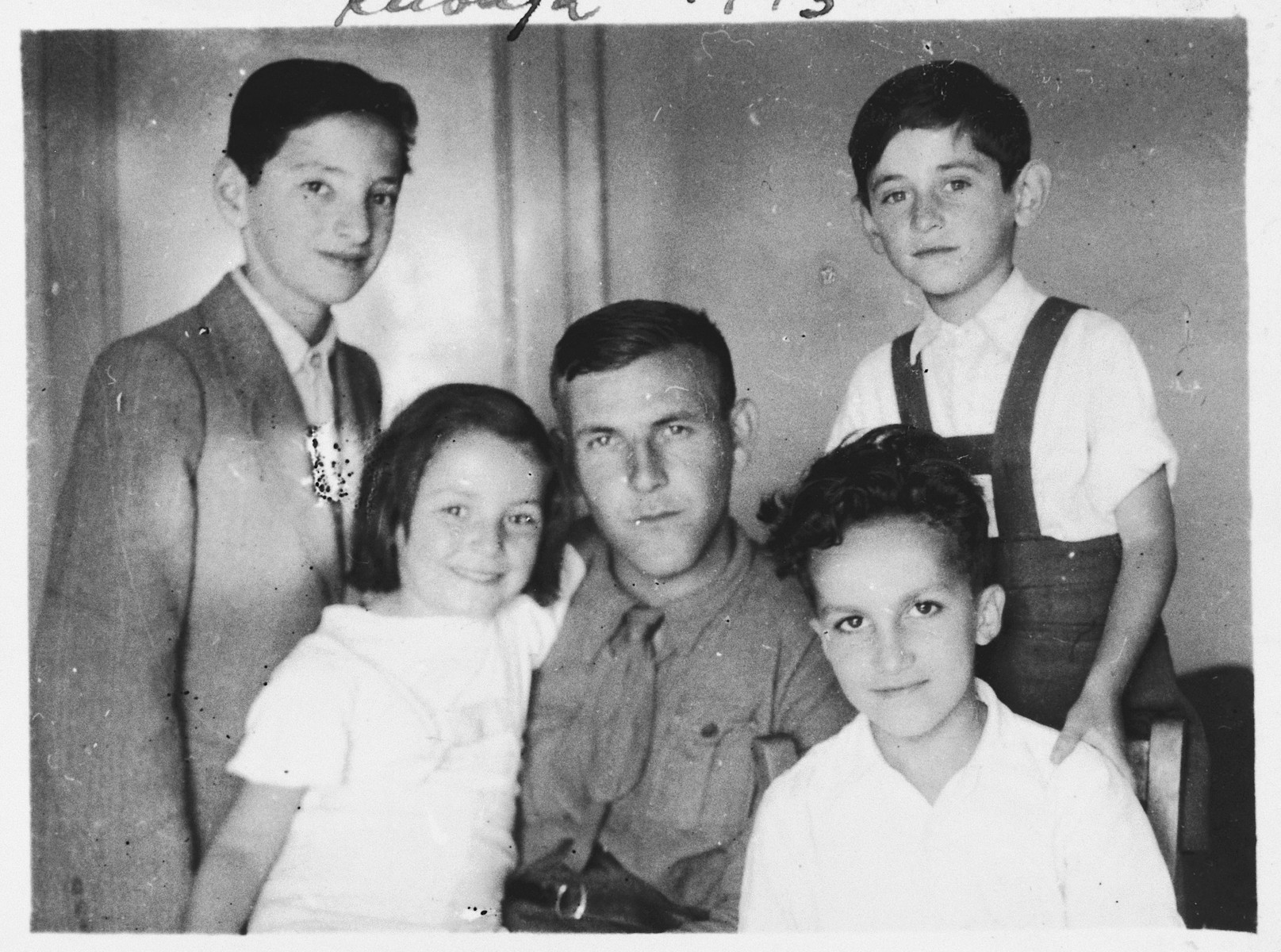 A group of Jewish refugee children living in an apartment house in Kavaja, Albania pose with an Italian soldier who is their tutor.  Among those pictured are Jasa Altarac (bottom, right), Gavra Mandil (top, right) and Irena Mandil (bottom, left).