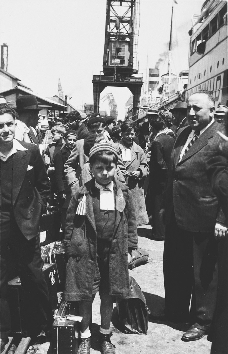 Albert Nussbaum, Director of Transmigration for the American Joint Distribution Committee stands next to a young boy who waits among a group of Jewish refugees to board the SS Mouzinho in the port of Lisbon.