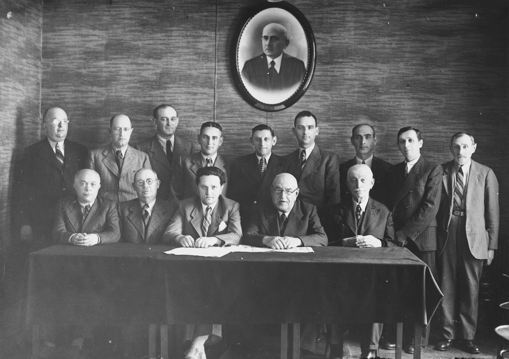 """Members of the board of directors of """"Achi Ezer"""", a welfare organization dedicated to helping refugees flocking to Lvov from the Ukraine.  Only two of those picutured survived the war.  Those pictured include front row: Israel Greenfeld (second from left), and Mr. Kaplan.  Back row: Joseph Silverman (third form left), Benzion Kwar (fourth from left), Charles Kfar (fifth from left; he was visiting from the United States) and Chazin (Meyer)."""