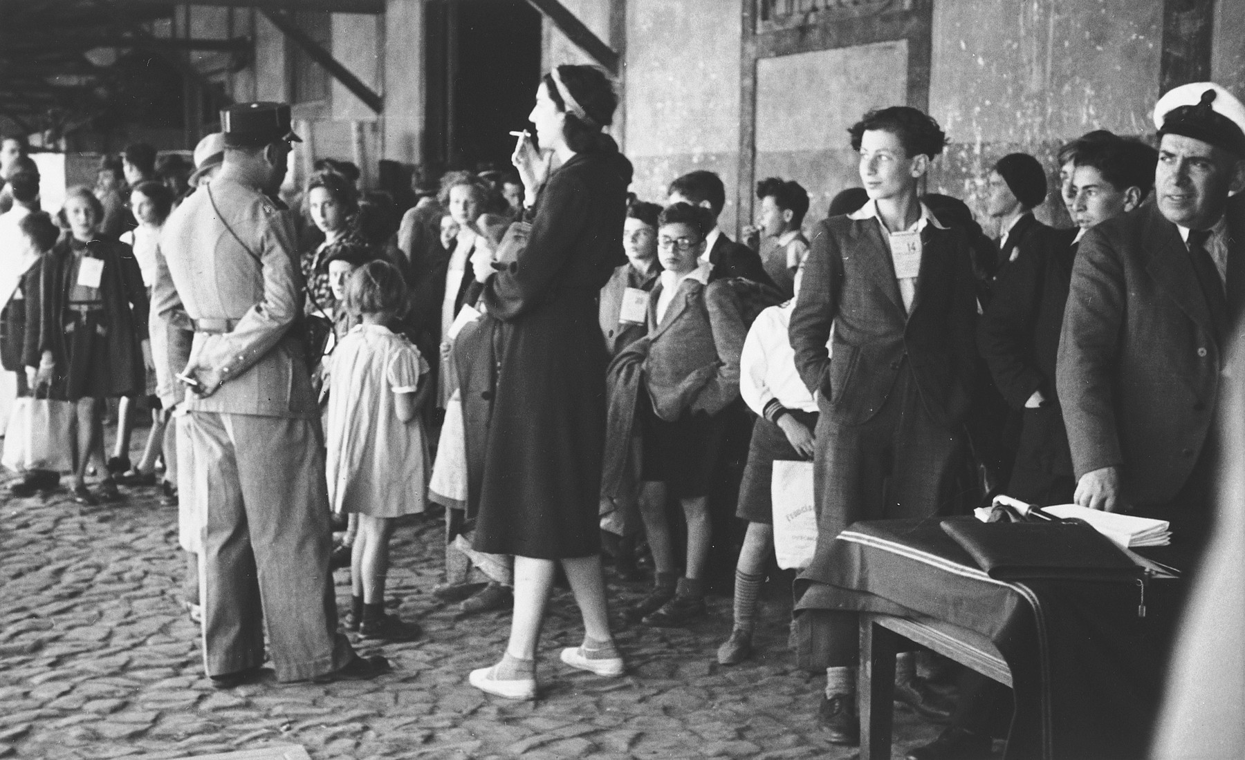 A group of Jewish refugee children wait in the port of Lisbon to board the SS Mouzinho.  On the right side of the photo a young man is wearing a tag clearly legible as #14. This is Guenther Sinasohn born 29 October 1926 in Germany. There was also a Herbert Schwartz (born 16 May 1925) on this transport who may have been Guenther's brother.The young blonde girl on the far left of the image is wearing tag #25, and can be identified as Lilian Warschawski (or Warszawski), born 20 April 1930 in Belgium.  In the middle of the photograph the young boy wearing what appears to be ID tag #23 is Oswald Kernberg, born 19 October 1929 in Vienna.  Pictured in the back, fourth from the right in profile is  Alexander Ssascha Britan. The tall woman smoking a cigarette might be Ursula Gajewska, who was the adult escort on this transport. Ursula was an American citizen, born 1908 in Buffalo, NY, who was fleeing Poland herself.