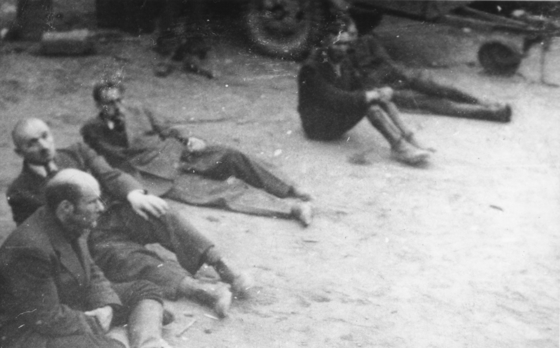Five captured SS guards sit on the ground in the newly liberated Dora-Mittelbau concentration camp.