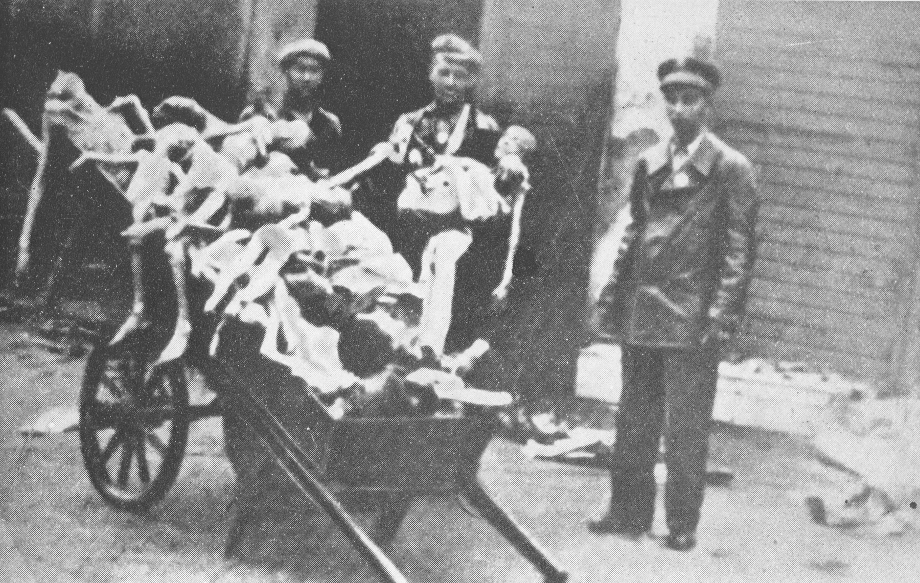 The bodies of emaciated children are piled in a cart before being taken out for burial.