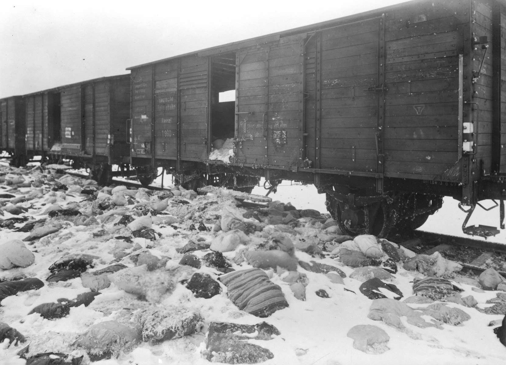 View of the abandoned train that was on the way to Germany loaded with the personal effects of Auschwitz victims.  Some of the freight  lies scattered and partially buried in the snow outside the train.