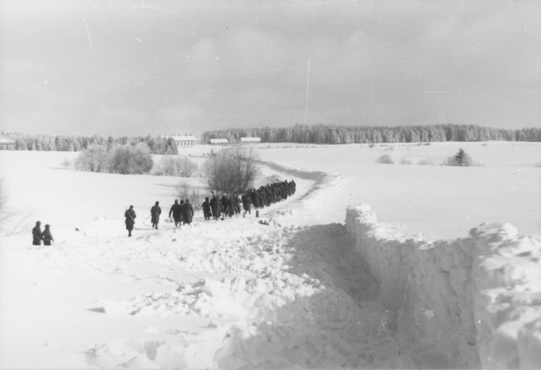 In the foreground stands a snow barricade built by Jewish conscripts in Company 108/57 of the Hungarian Labor Service to prevent snow from drifting onto a road.  In the background, the Company is returning to the camp for the day.
