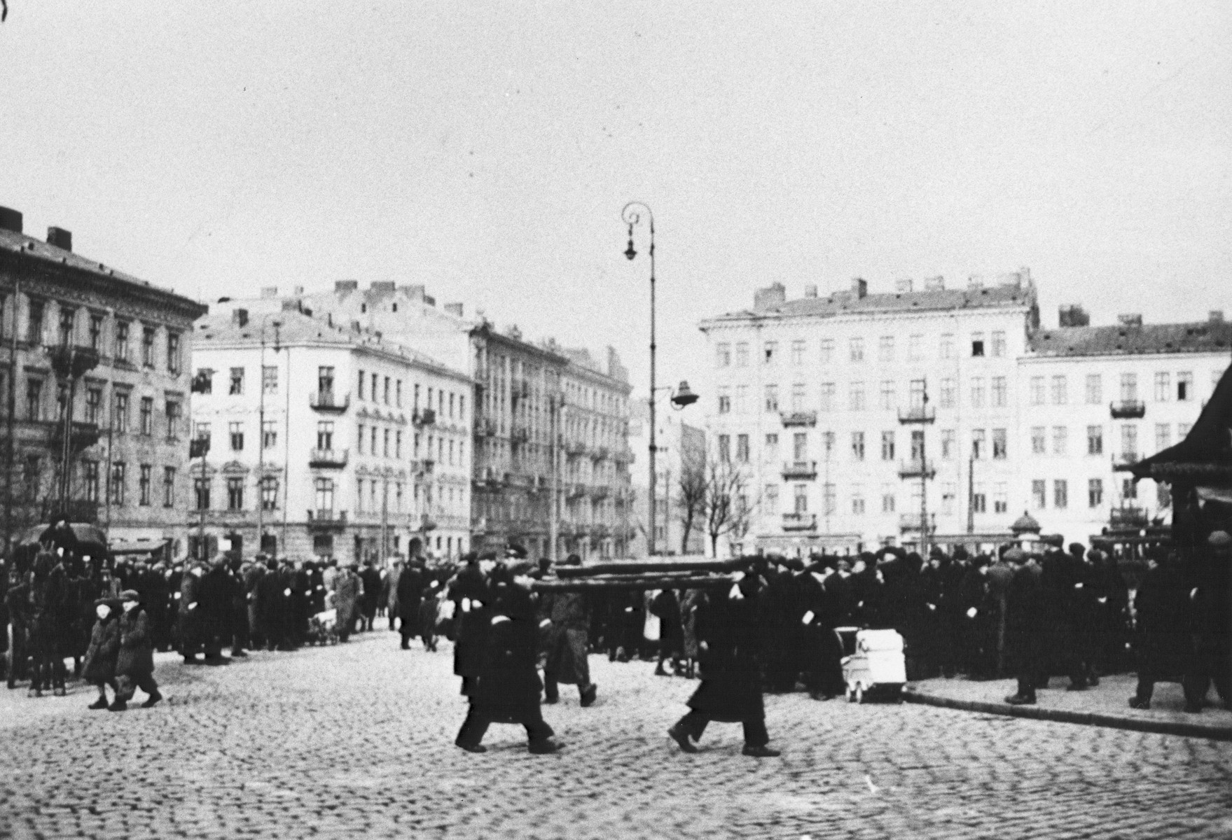 Jews are gathered in large numbers in a public square in the Warsaw ghetto.