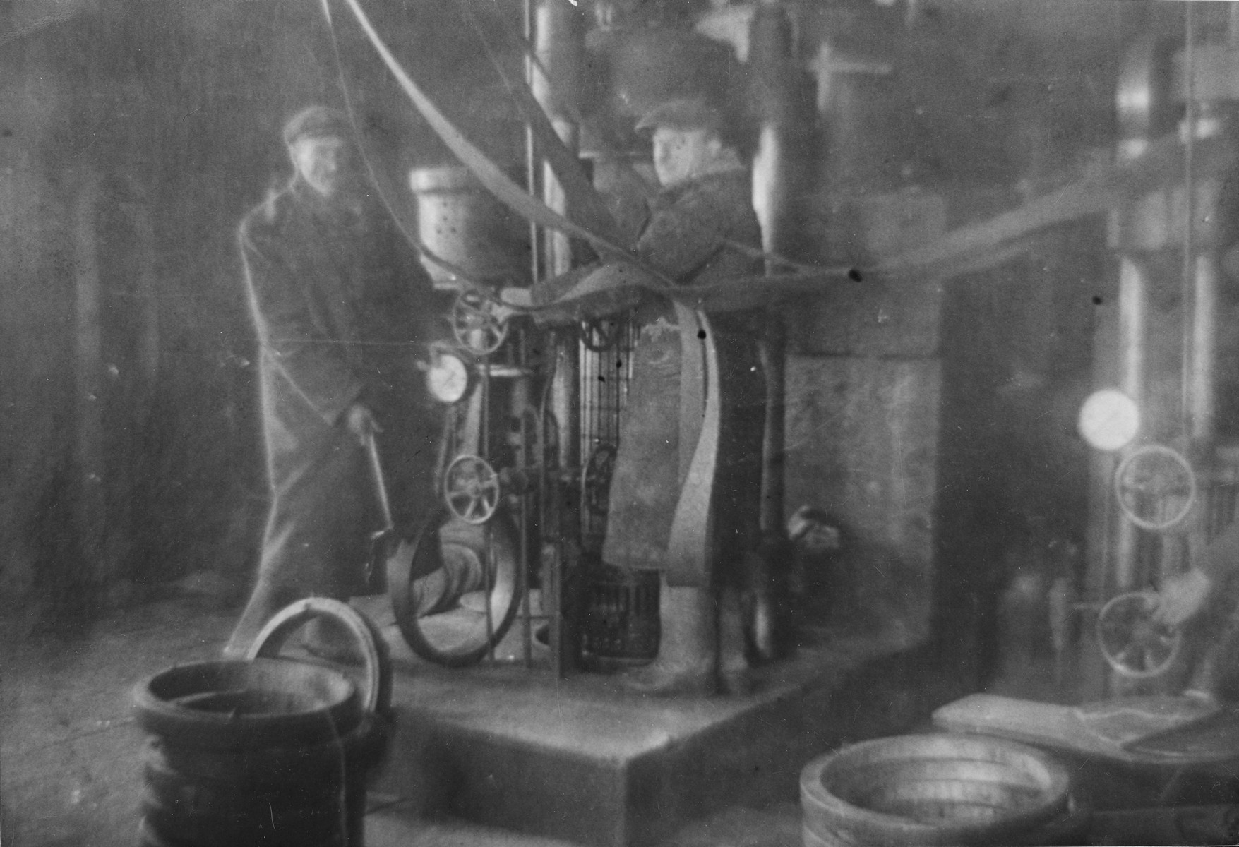 Jewish men working at an oil press in the Glubokoye ghetto.  Among those pictured is Moshe Katz.