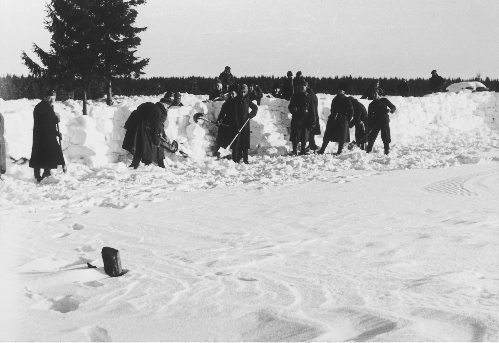 Jewish conscripts in Company 108/57 of the Hungarian Labor Service at forced labor constructing a barricade to prevent snow from drifting onto a road.
