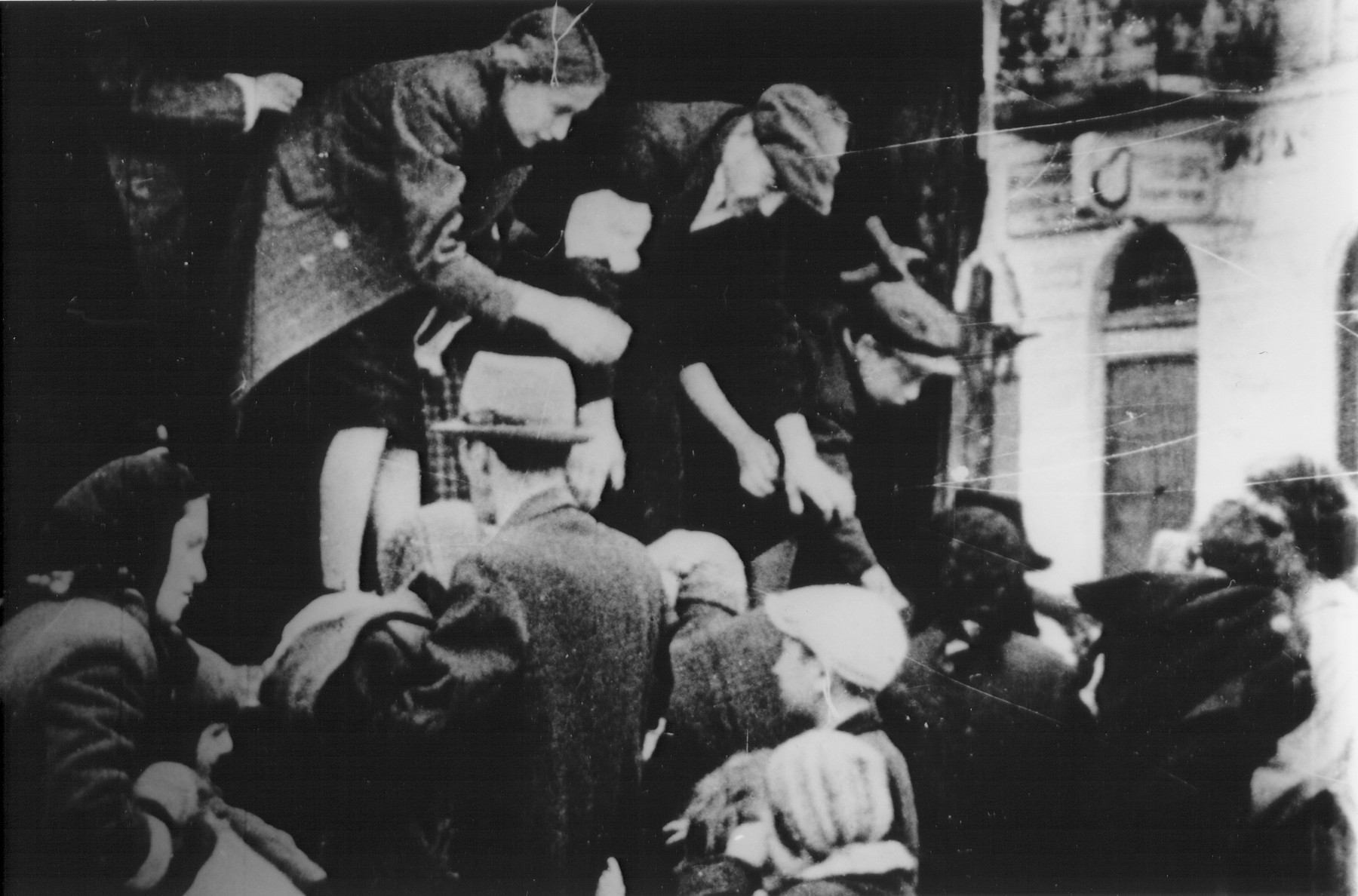 Jews captured by the SS during the suppression of the Warsaw ghetto uprising board a truck.