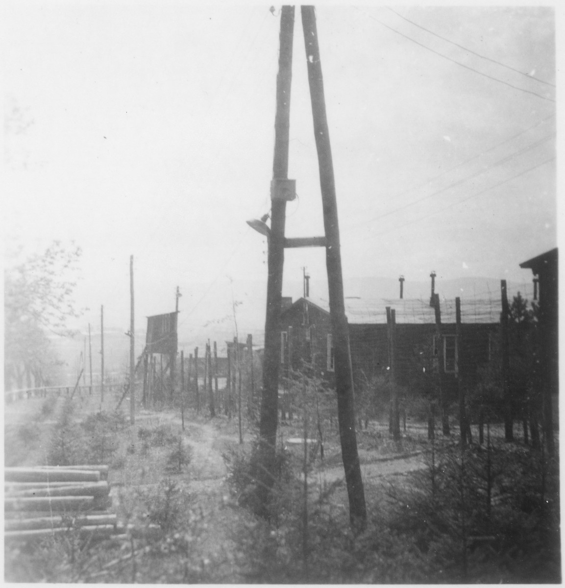 View of a guard tower and the barbed-wire fence that enclosed the Ohrdruf concentration camp.