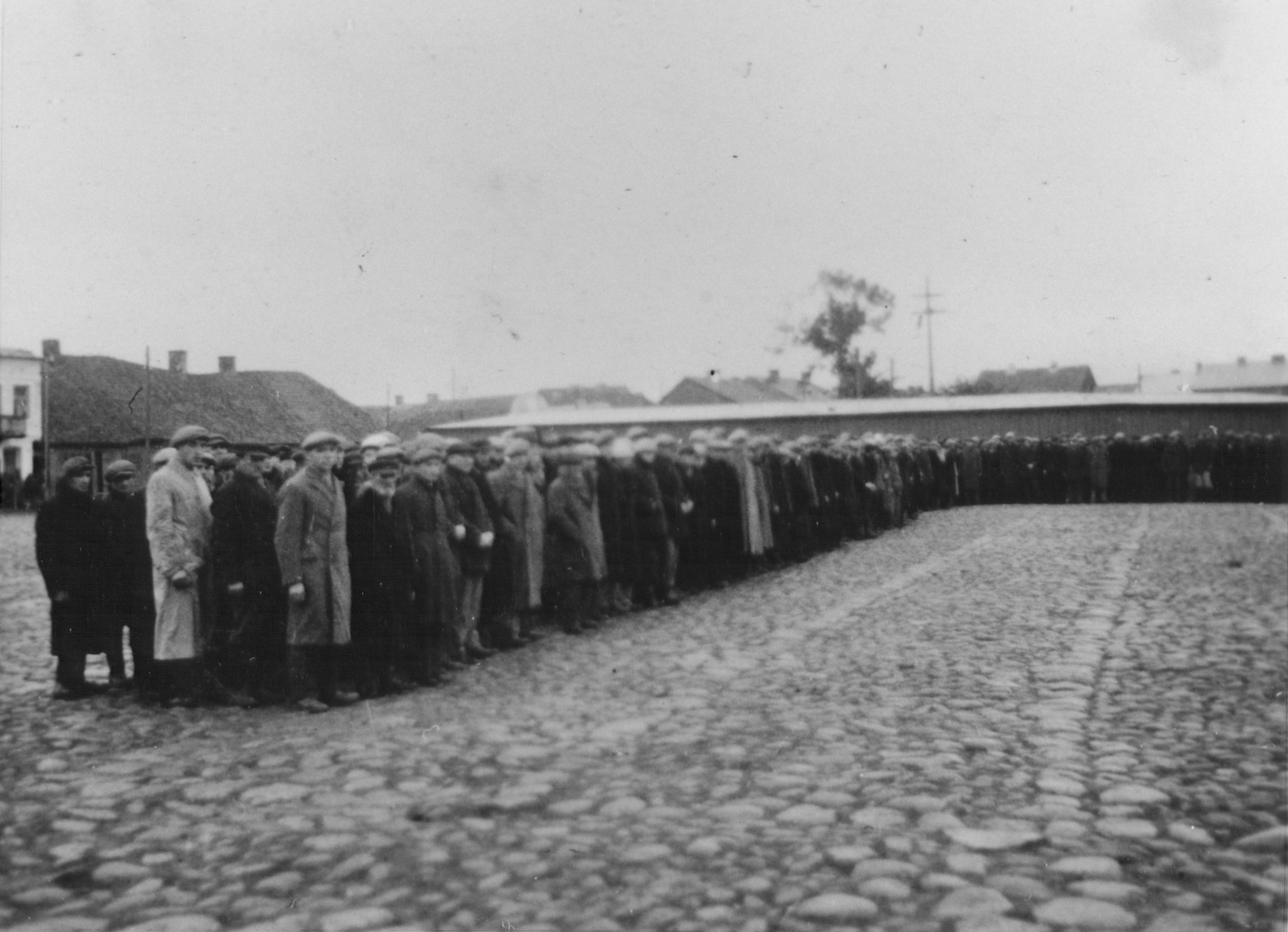 Jewish men are lined up along the perimeter of the town square in Raciaz.