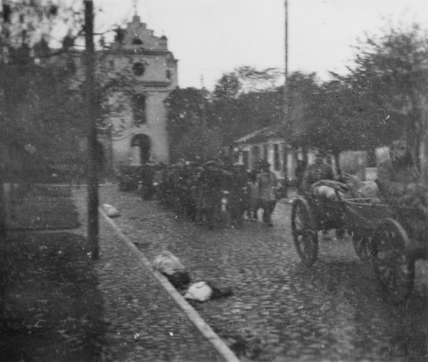 A column of Jews walks behind a wagon on a cobblestone street during a deportation action in the Wisznice ghetto.