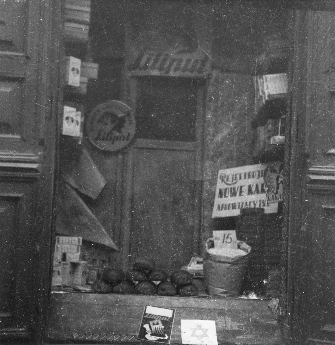 "Close-up of a shop window in the Warsaw ghetto.   Joest's original caption reads: ""Fresh loaves of bread were stacked up in a window.  A bucket of beans.  Packages of Liliput baking powder.  And a sign that new 'ration cards' were being accepted here as well."""