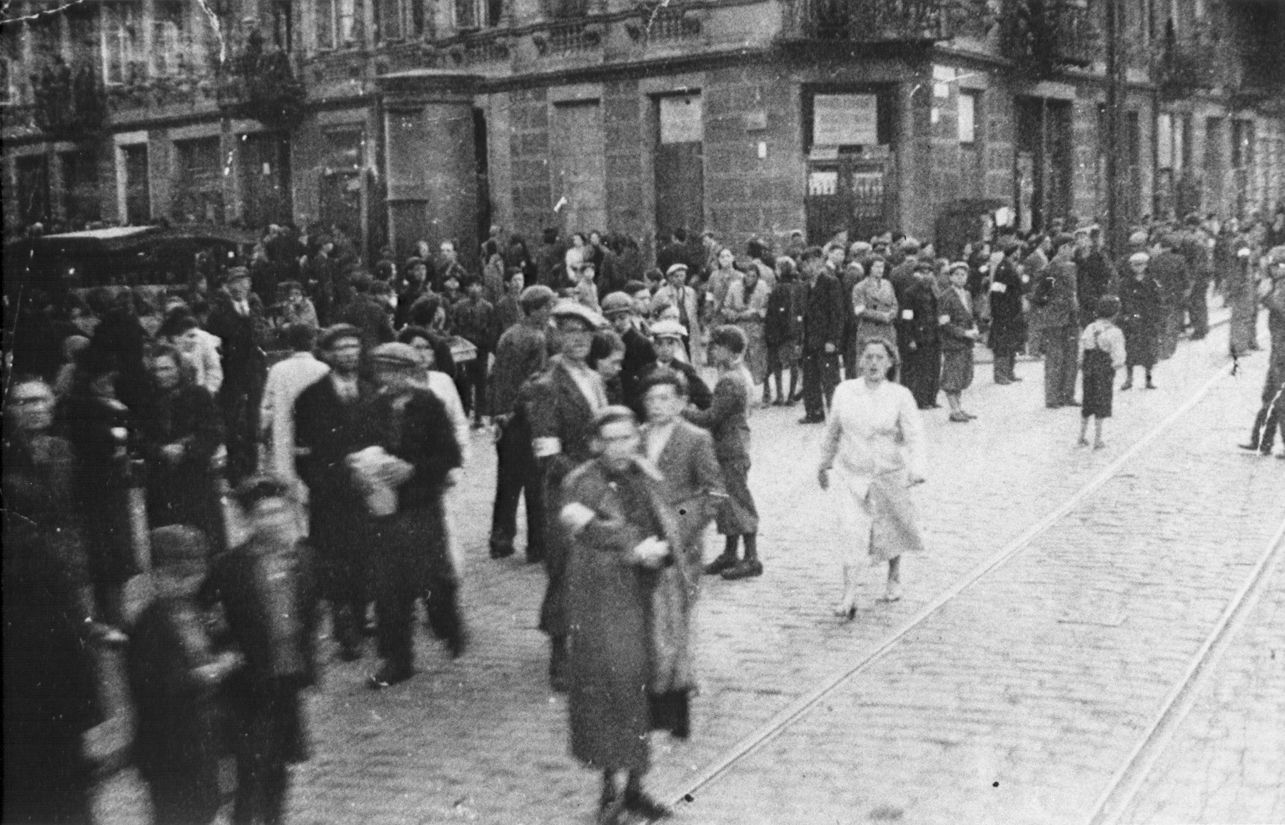 Large numbers of Jews walk along a street in the Warsaw ghetto.
