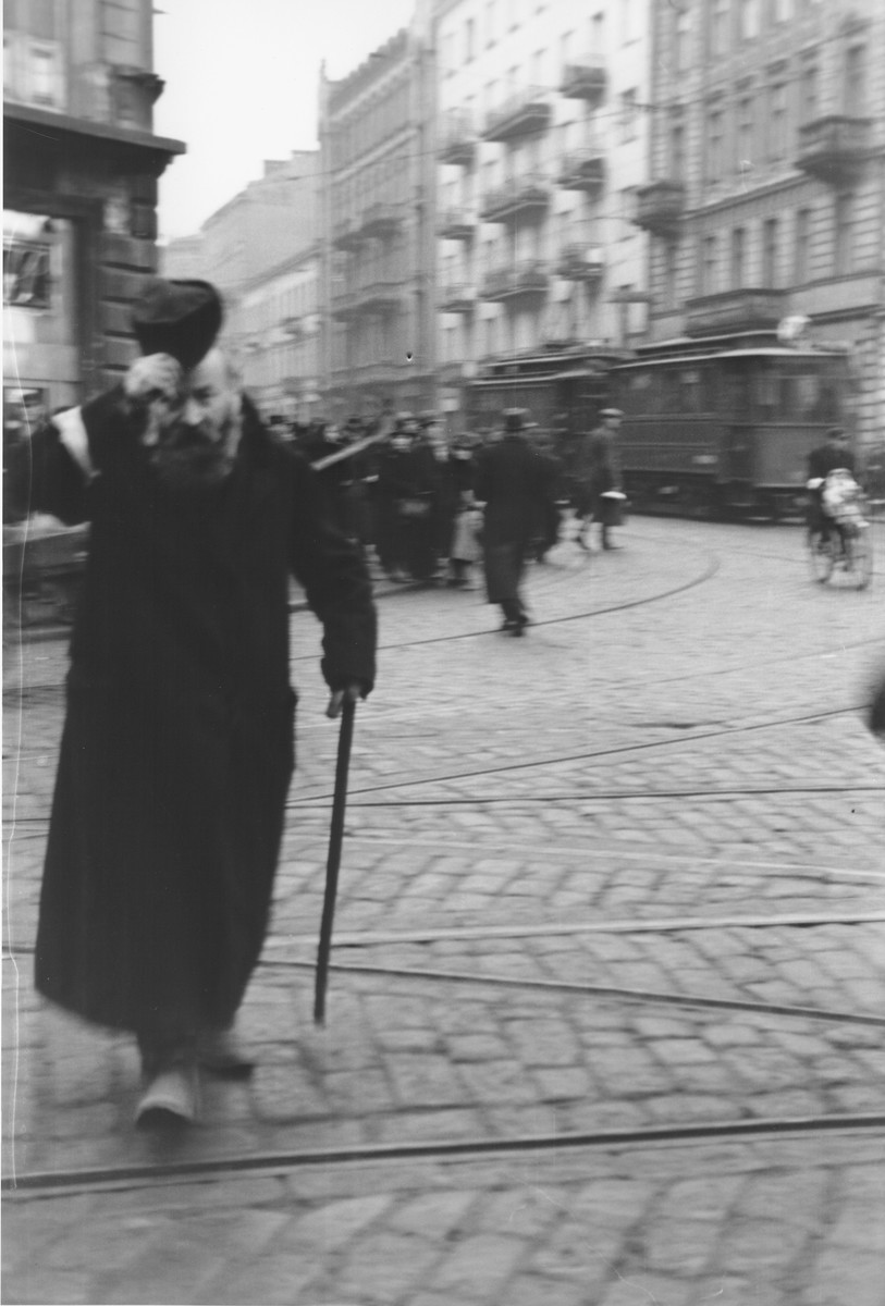 A Jewish man crossing the intersection of Chlodna and Zelazna streets in the Warsaw ghetto doffs his hat to the German photographer, Willy Georg.