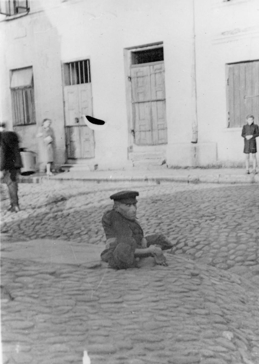 A destitute Polish Jew in an unidentified ghetto in Poland.