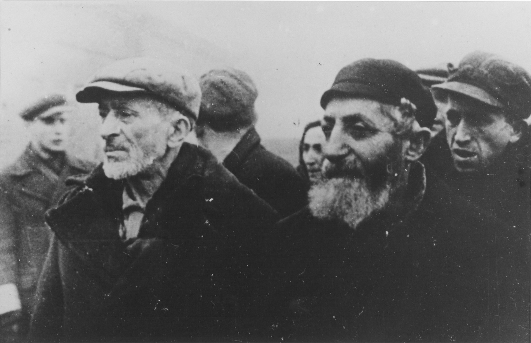 Close-up of Jewish men standing in a column in the Warsaw ghetto.