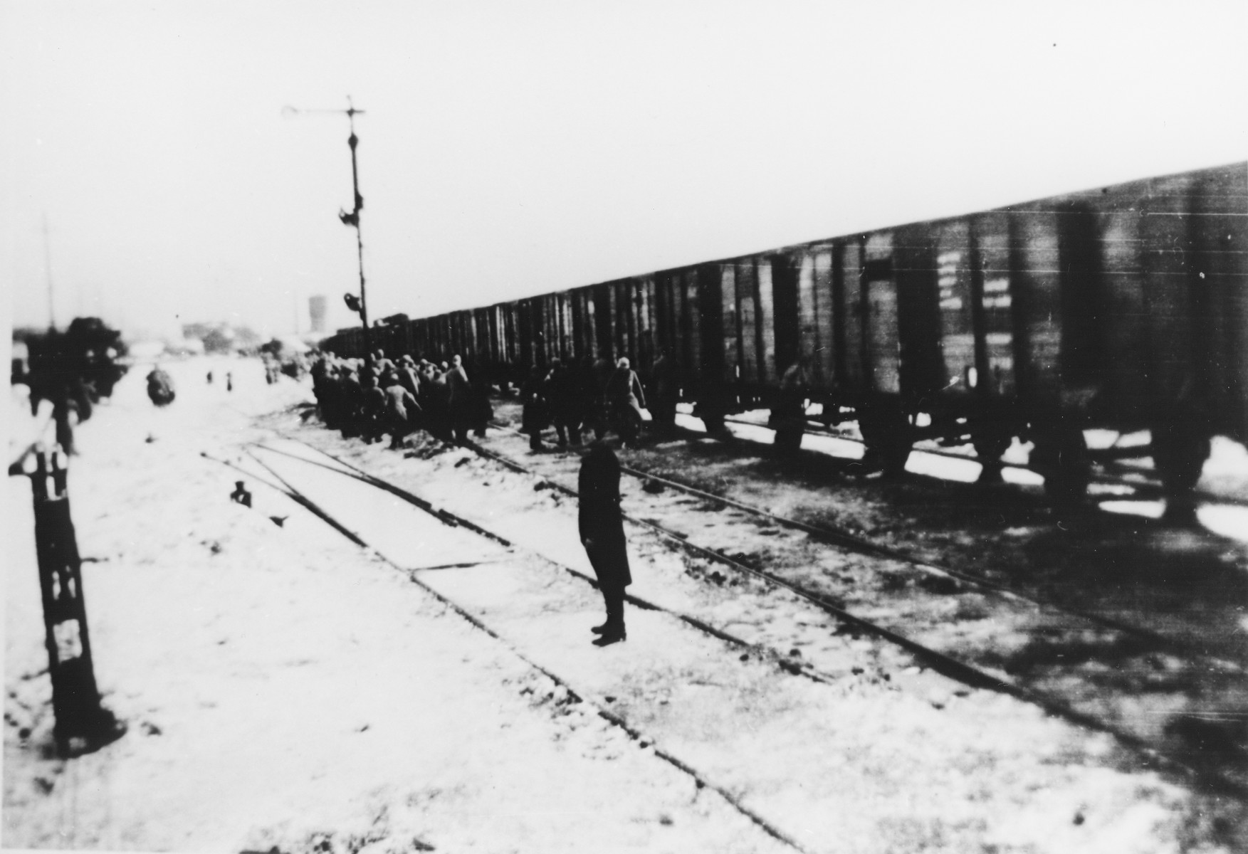 A German stands guards on a snow-covered railroad track as a group of Jews are led to a deportation train.