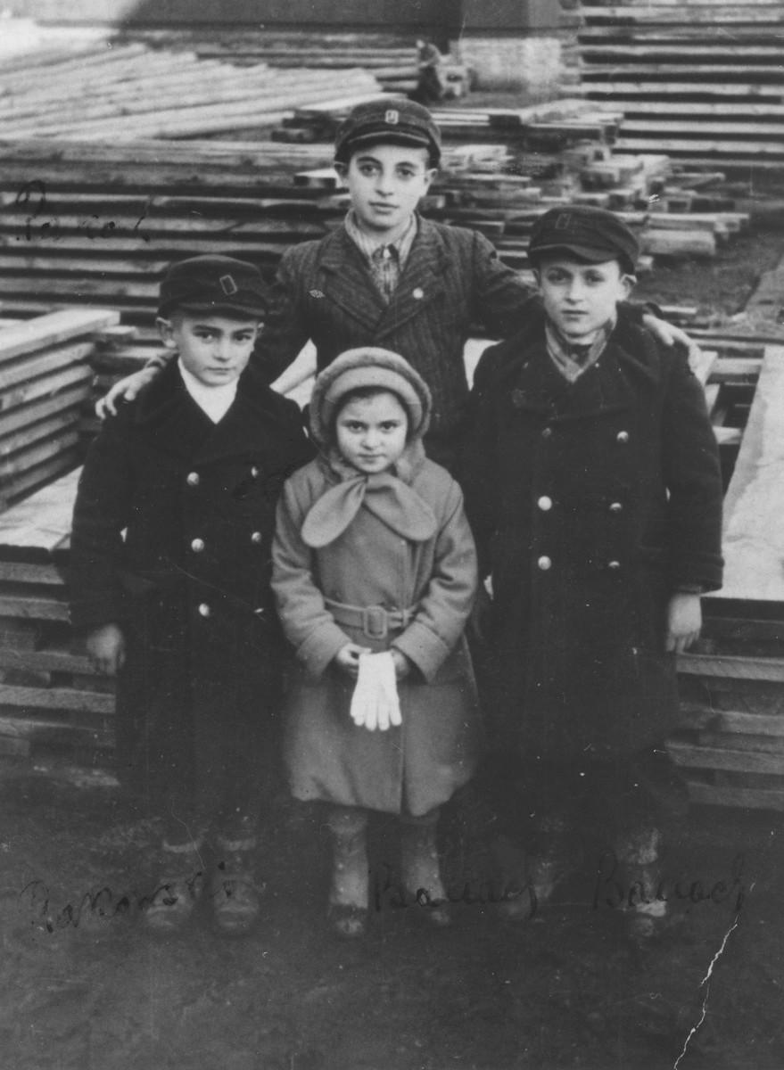 Four Jewish cousins pose in a family-owned lumberyard in Kazimierza Wielka.  Pictured clockwise from the top are: Shmuel Rakowski, Samuel Banach, Masha Dina Banach and Israel Rakowski.  Masha Banach (b. 1930) was the only prisoner who died while working at Oskar Schindler's factory in Krakow-Zablocie.  She succumbed to disease.