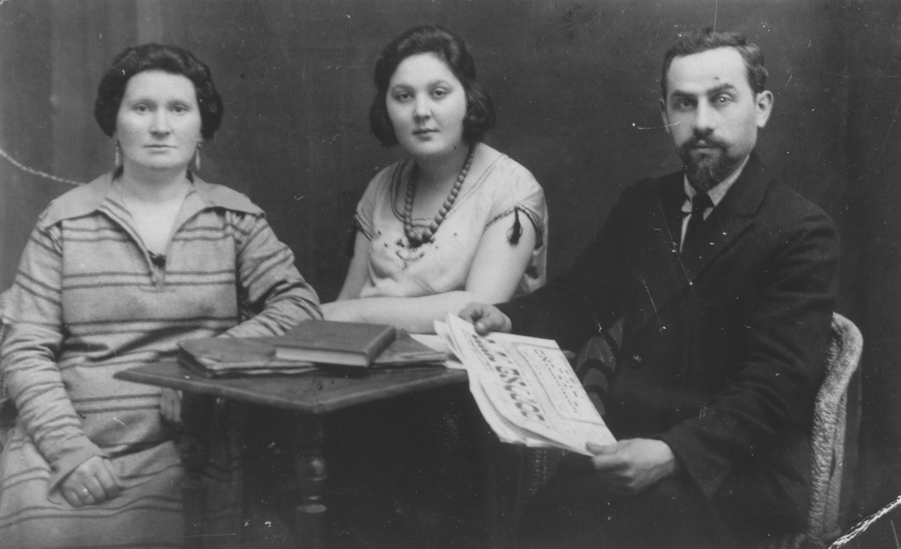 Studio portrait of the Ajzner family.  Pictured from left to right are Chaja Ester, Malka Bella and Noah Ajzner.