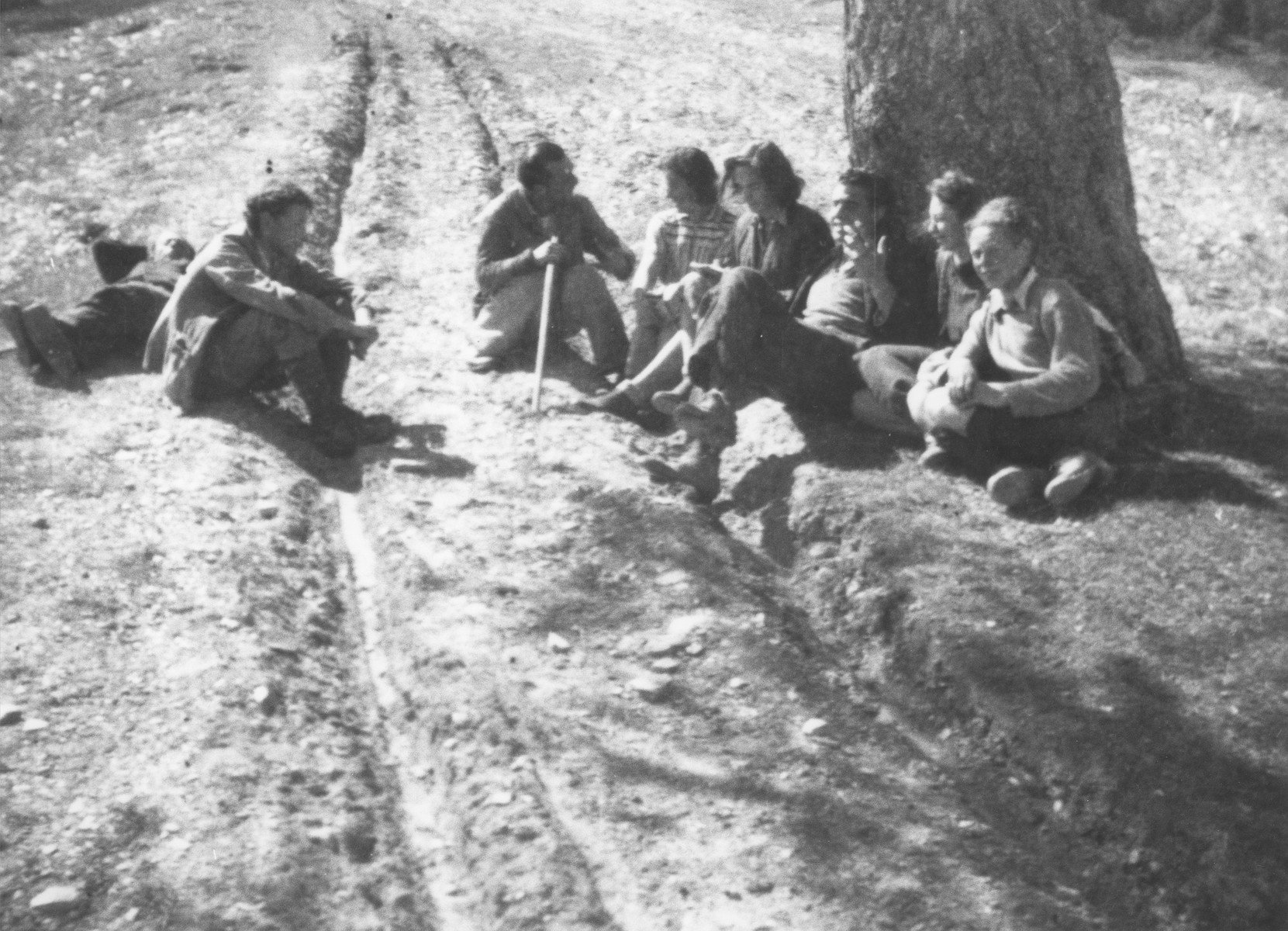 Jewish refugees rest beneath a tree during their escape over the Alps to Italy from the Italian-occupied zone in France following the signing of the Italian armistice.  Carl Roman and his mother are pictured on the far right.
