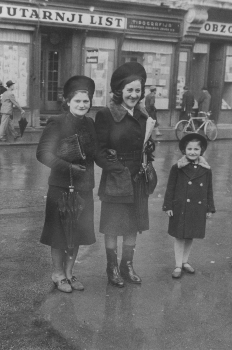 Two Jewish women pose with a child in front of a newspaper office on a street in Zagreb.  Pictured are Emma Romano (left), her daughter, Rena (right) and an unidentified friend (center), who later perished during the war.