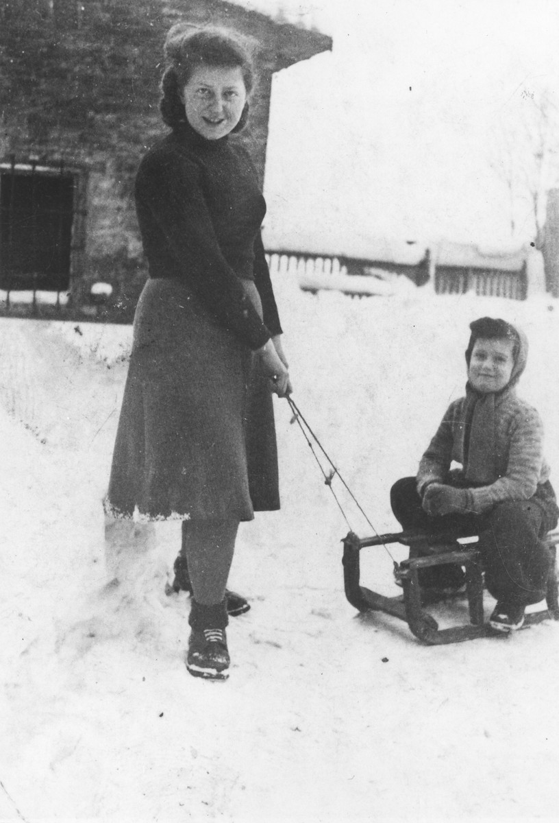 Renia Zylberszac pulls her sister, Mira on a sled in the Dabrowa ghetto.
