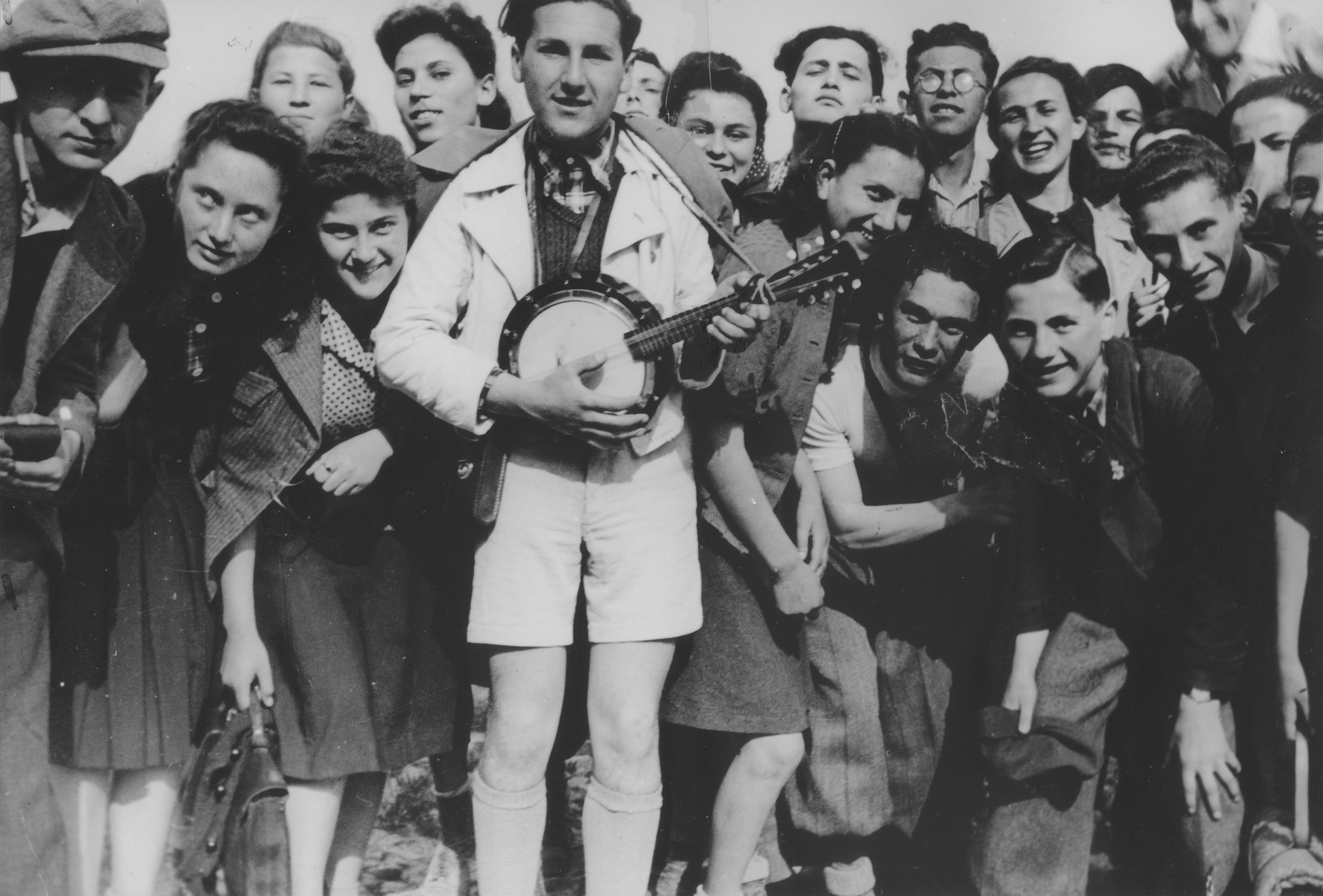Gyuszi Lovi plays the banjo for his fellow students at the Hebrew gymnasium in Mukachevo during a Lag b'Omer holiday celebration.  Those pictured include Eugen Schoenfeld (Tuli), Olga Joszef, Olga Weiss, Gyuszi Lovi, Lajos Bodek, Ervin Stern, Gyongyi Kirshenbaum, Hersi Birnbaum and Agi Mermelstein.  Neurath is pictured in the back with glasses and Guttman is at the bottom right.