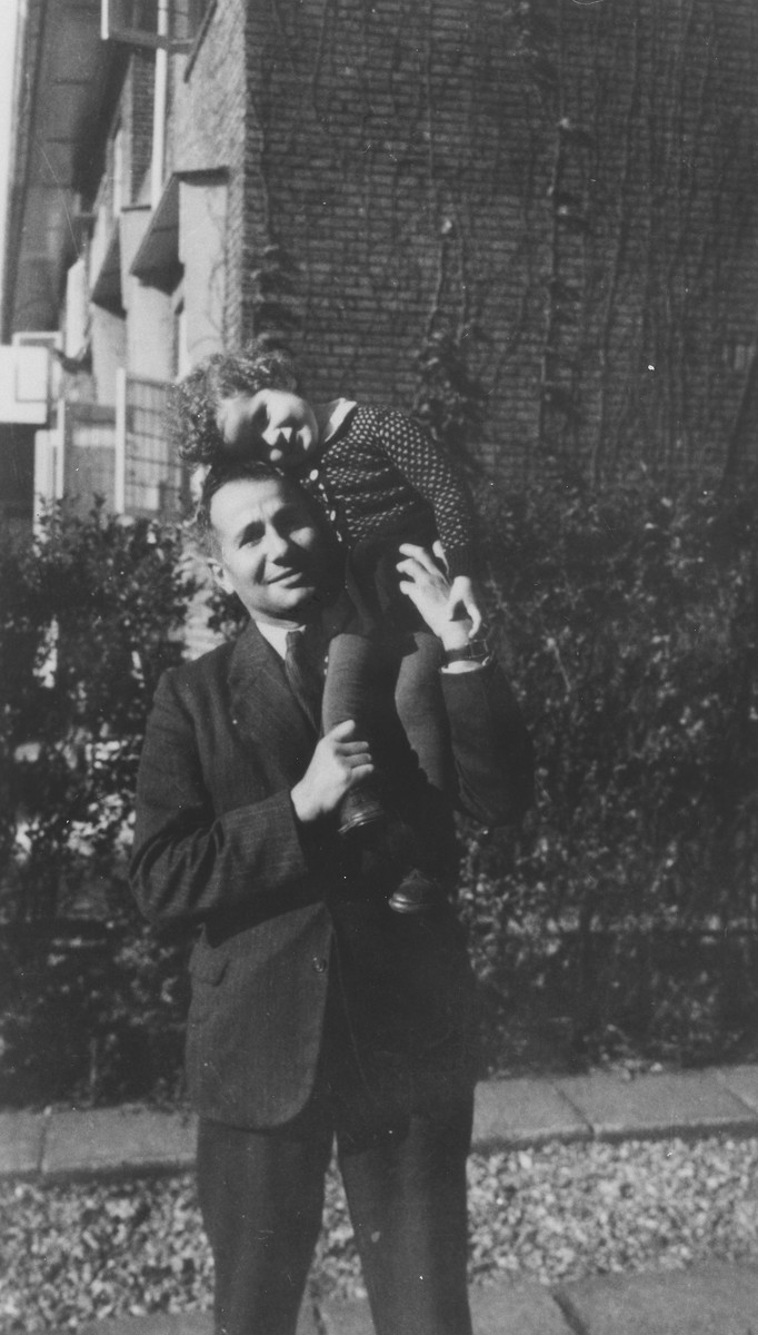Manfred Grunbaum holds his daughter, Dorien, on his shoulder shortly after their return to Holland.