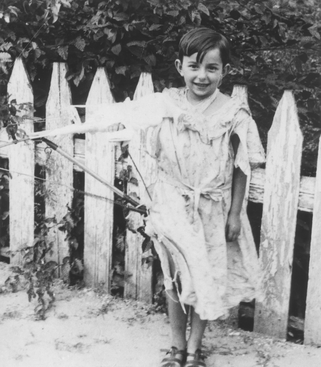 A young Jewish girl poses by a garden fence.  Pictured is Chaja Garbasz, who later perished in the Holocaust.