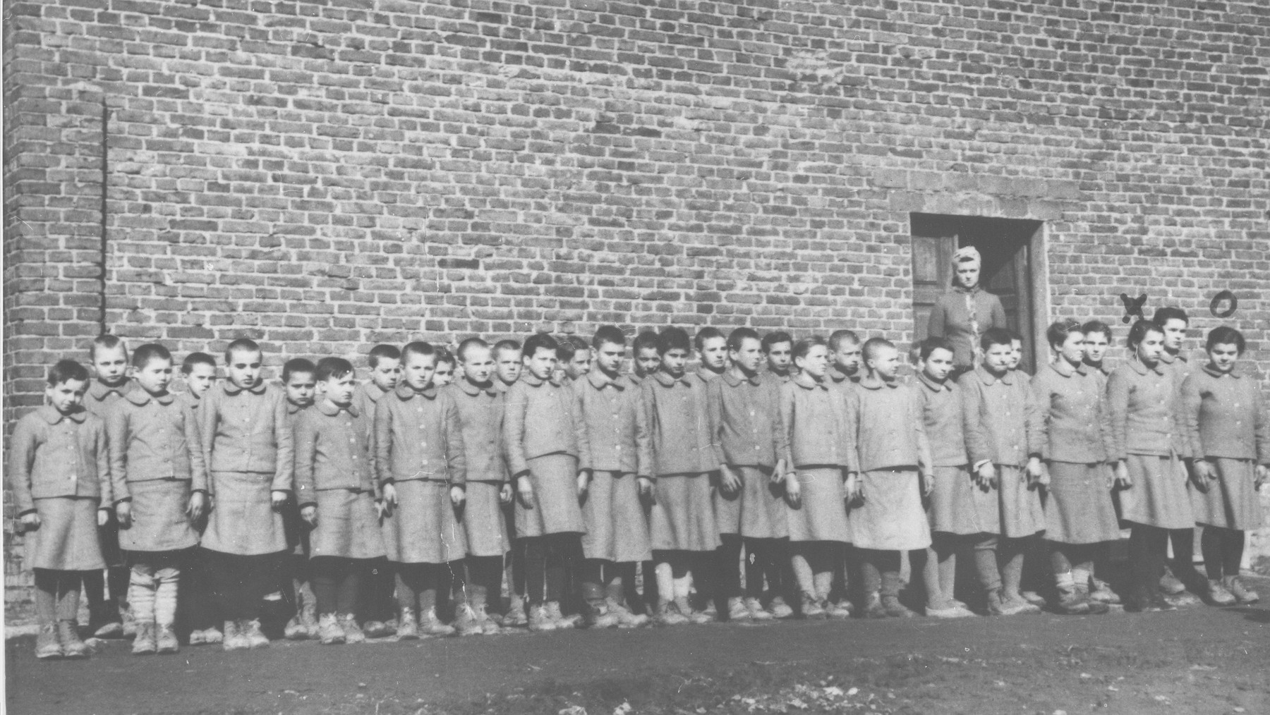 Girls are assembled for roll call at the Jugendschutzlager Litzmannstadt, a concentration camp for Polish juveniles.  Behind them stands the camp commandant Eugenie Pohl.