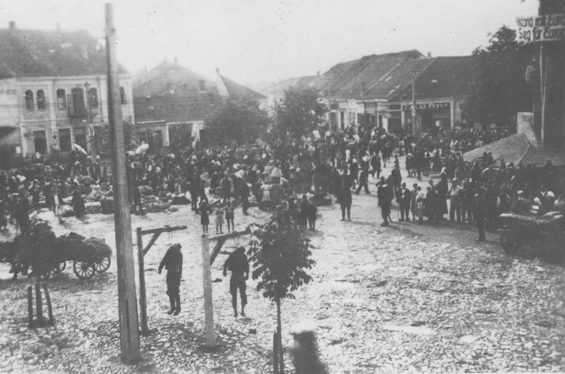 Two Serbian partisans executed by German soldiers hang from a gallows in the town square of Kraljevo.