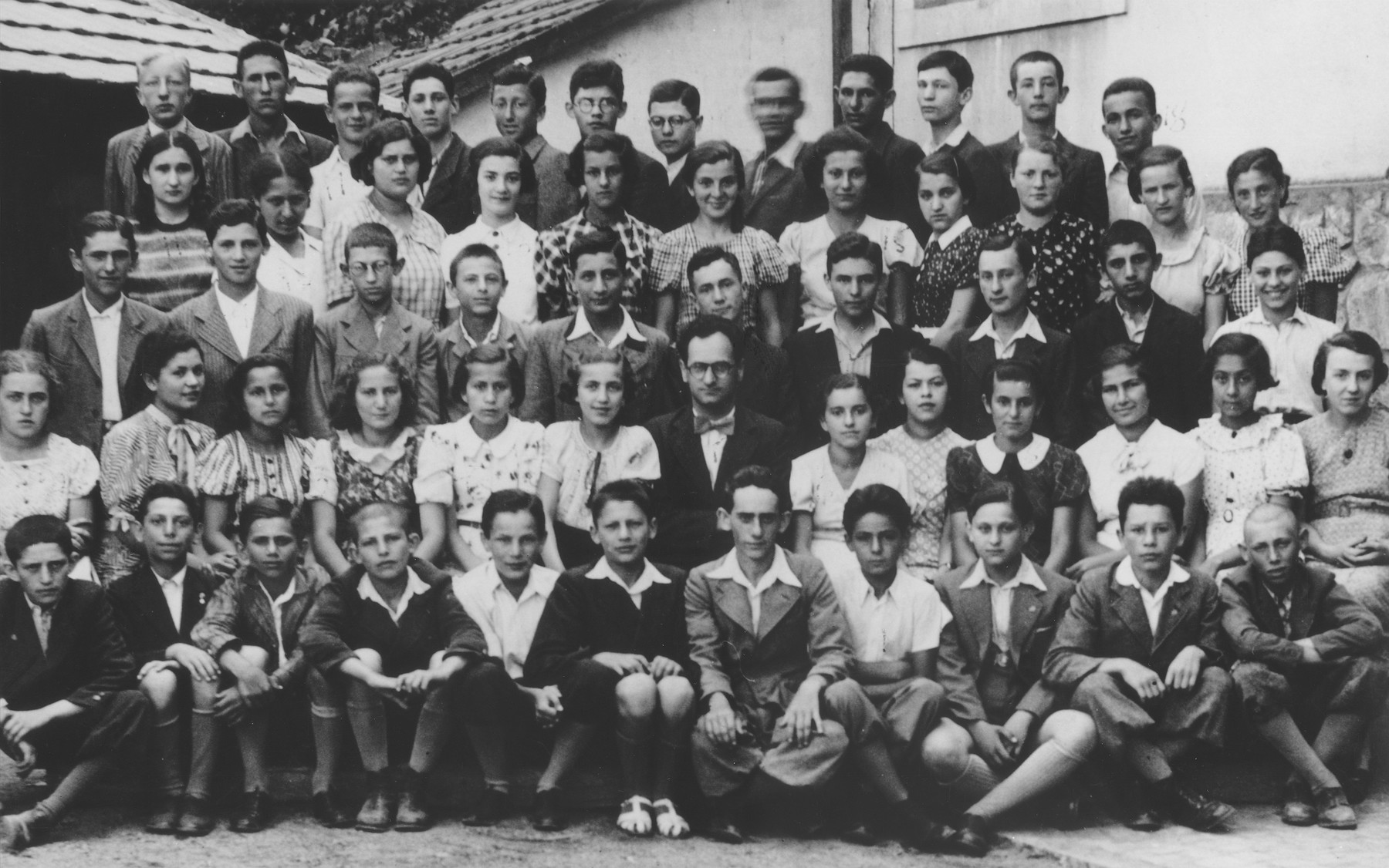 Group portrait of students and teachers at the Hebrew gymnasium in Mukachevo.  Those pictured include: First row (left to right) Jeno Goldberger, Kopolovich, unknown, Mermelstein, Kopolovich, Friedman, Josef Mordechai (Mattju) Gottesman, Taci Joszipovics,   [possibly] Tibor Gottesman, Greenberger, and Abraham.  Second row: Sari Haupt, Babuci Birnbaum, Vera Berkovich, Sidi Grunstein, Lola Sternbach, Mimi Enneman, Jeno Morvai (teacher), Goldi Gluck, Patyu (Shoshanan) Friedman, Richie Seidenfeld, Friedman, unknown, unknown.  Third row: Laci Weinberger, Hersi Birnbaum, Klein, Mermelstein, Birnbaum, Hermanovich, Judu Muhlrad, Ringler, unknown, Tobias.  Fourth row: Oti Rubin, Agi Block, Gottesman, Ibu Schonberg, Alice Kornreich, Mermelstein, Ruki Jakober, Hoenig, Eva Schonfeld, Nancsi Berkovics and Friedman.  Top row: Unknown, Neuman, Berkovitz, Bela Zelemovich, Andrew Stern, unknown, Gross, Rudolf Farbenblum, Safar, Feri Fullman, Klein, and Zvi Steiger.