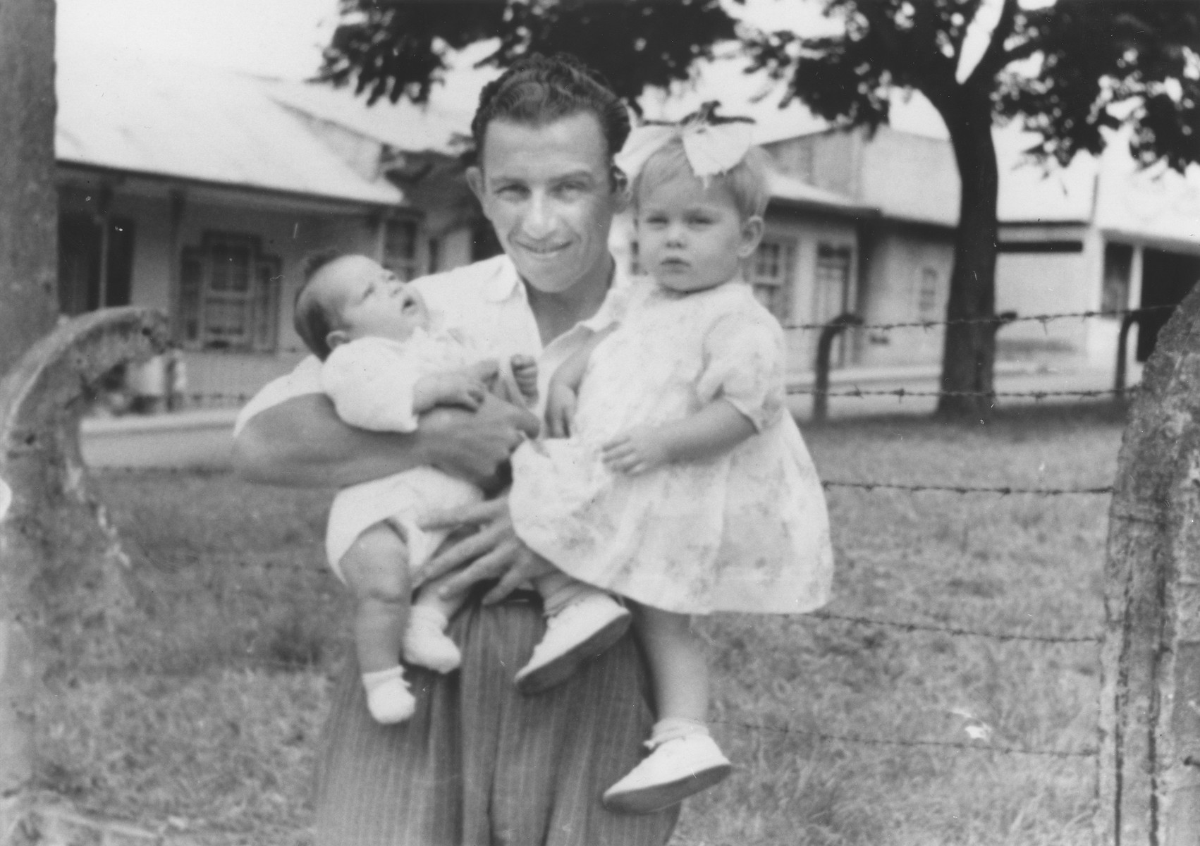 Portrait of Lezer Kawer holding his two children, Dina and Noah, outside their home in Costa Rica.