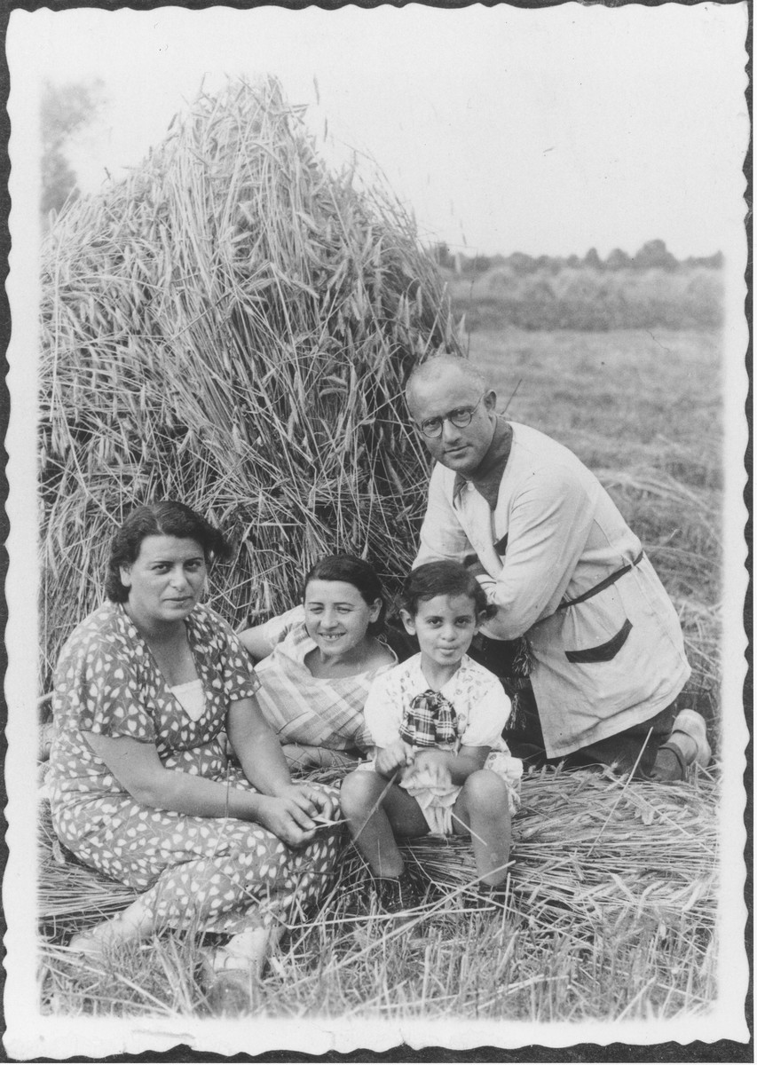 The Berkowicz family poses in front of a haystack on a farm [probably in Nadolnik, Poland].  Pictured from left to right are Bina (Taca) Berkowicz, her sister Fela (Taca) Bursztyn, Basia Berkowicz and Chaim Ber Berkowicz.