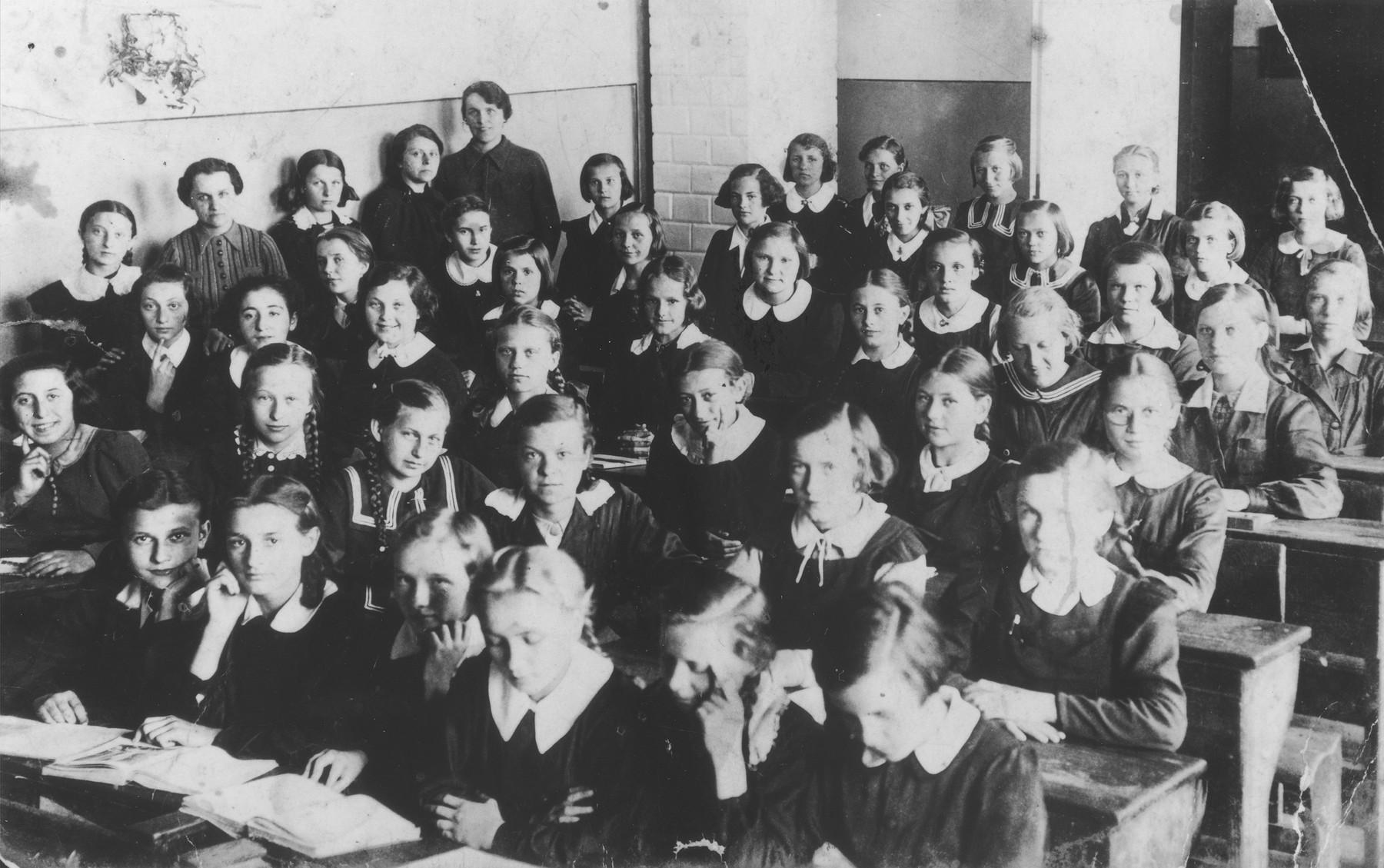 Seventh grade students and teachers pose in their classroom at the public school on Narutowicza Street in Dabrowa Gornicza.    Among those pictured are Pola Rozen; Frania Magierkiewicz; Hanka Lewkowicz; Zosia Putersznyt, Sala Szmeker; and the teacher, Mrs. Kaufiszer.