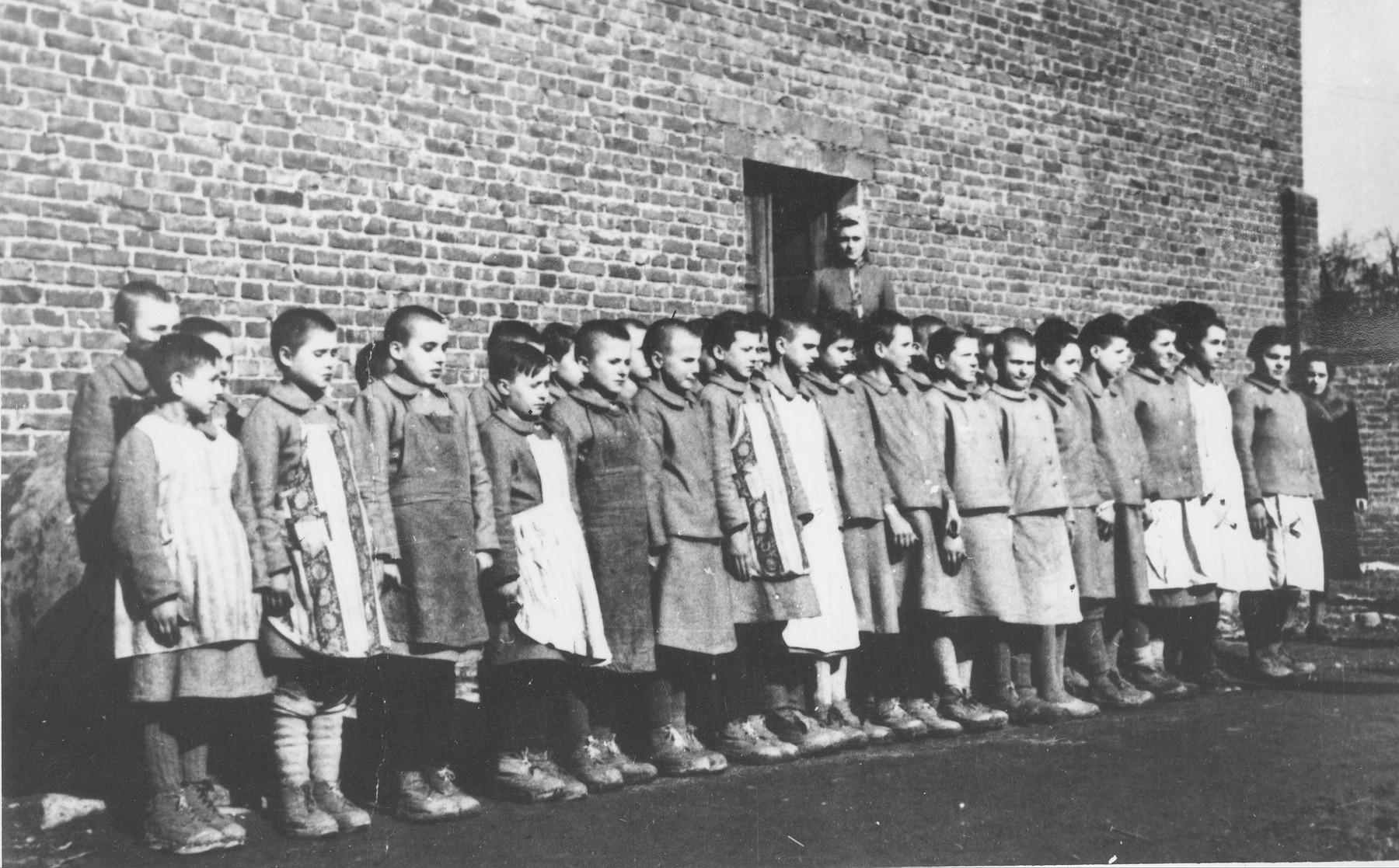Girls are assembled for roll call at the Jugend- schutzlager Litzmannstadt, a concentration camp for Polish juveniles.  Behind them stands the camp commandant Eugenie Pohl.