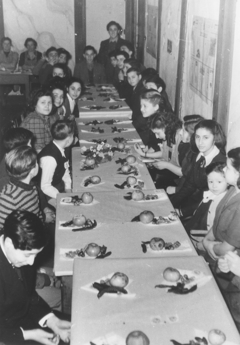 Jewish DP children celebrate Tu B'Shvat at a seder in the Siebertsrasse school in Munich.  Among those pictured are the donor's cousins, Henry Ziv (bottom left) and Fenny Olitzki (left side, sixth from the front).