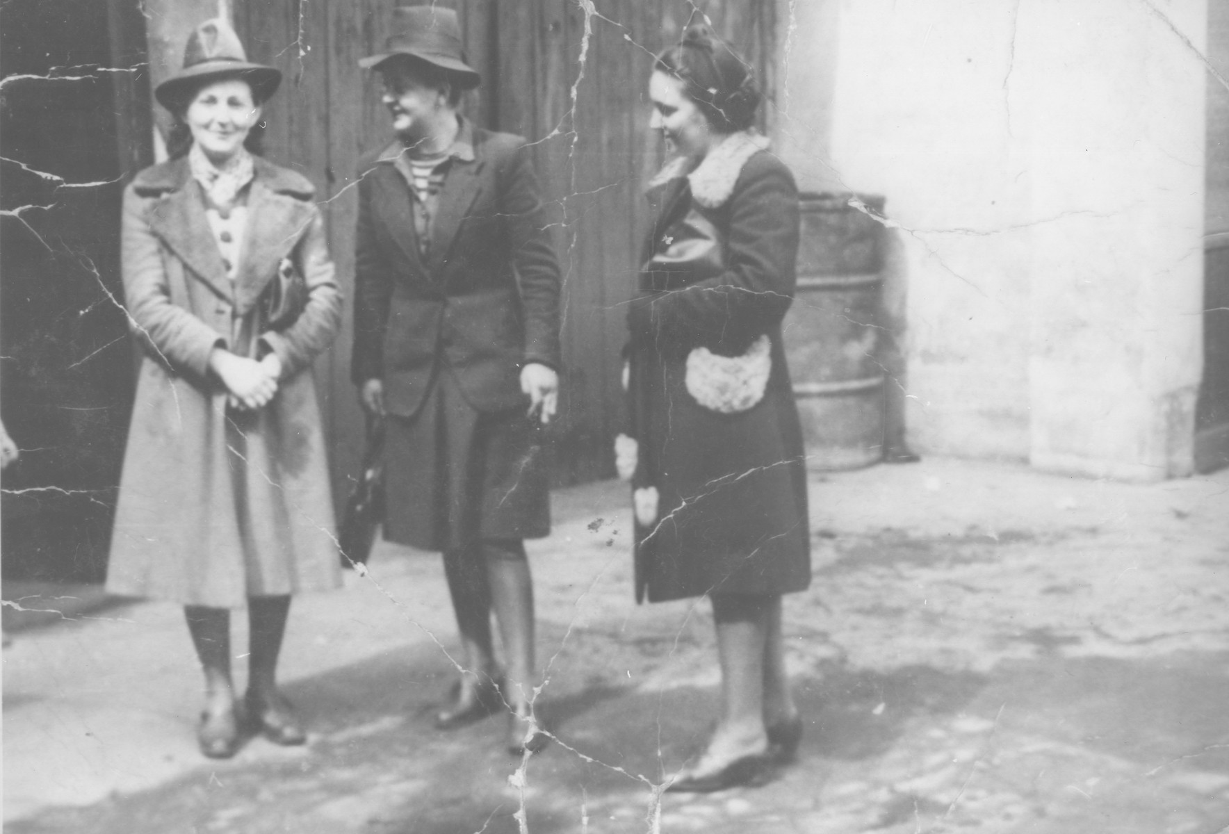 Three Jewish women who are posing as Poles, stand in a courtyard on the Aryan side of Warsaw.  Pictured are Fela Katz (center), the donor's sister, with her cousin, Franka (left) and a friend, Lola Bleiberg (right).