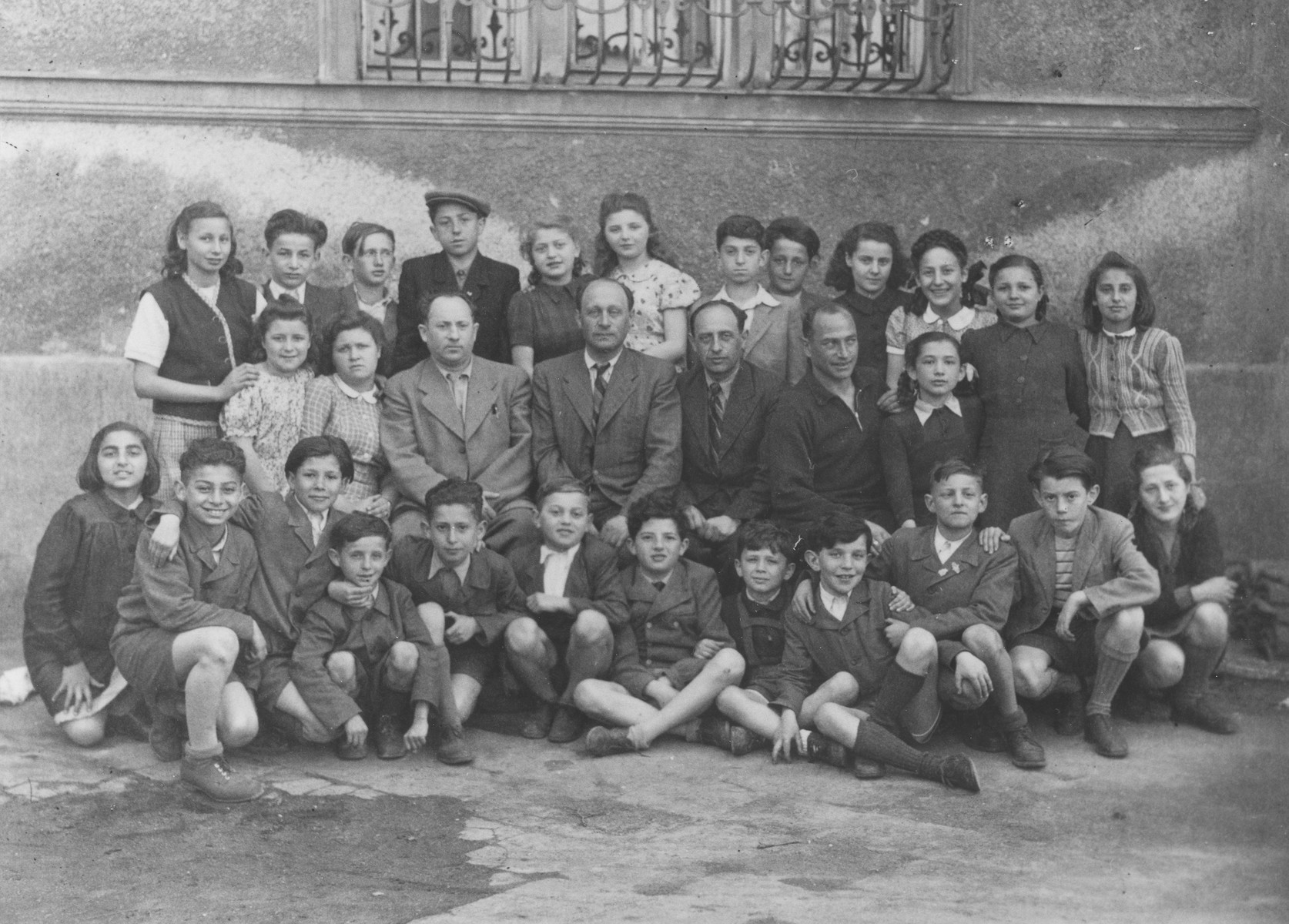 Group portrait of Jewish DP students and teachers at the Moehlstrasse school in Munich.  Among those pictured are Ellen Griliches (back row at the far left); Max Wekselman (back row 3rd from left); (Shloime Rabinowsky (back row, fourth from the left); Rozia (Shoshana) Grossman (back row, sixth from the left); Aron Bankowicz (back row, seventh from the left); Bronia Zwass (back row, first from the right); Gunia Herring (third row, first on the left); Dina Friedman (front row, first on the right).