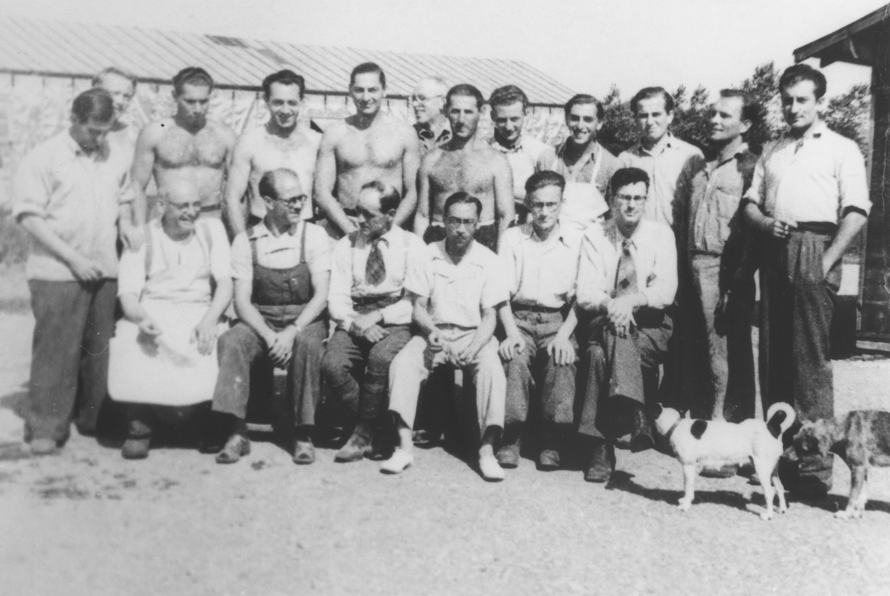 Group portrait of foreign workers assigned to the food supply department at the Gurs internment camp.  Two of those pictured, Bustamante and Vigo, were former members of the Spanish Republican army.  Vigo had been the mayor of Badalona.  All the others were Jewish.   Seated from left to right are Jakob Dreyfus, Bustamante, Francois Marine, Pedro Vigo Giro, Szlama Szmaragd and René Karschon.  Standing are Vogelsang, Walter Todt, Ossi Kohut, Sepp Grumkin, Hayek, Reinach, Alex Gruber, Franz Wrobel, Pauli Kupferberg, Kurt de Jonghe, Zaiakowski and Kurt Mautner.