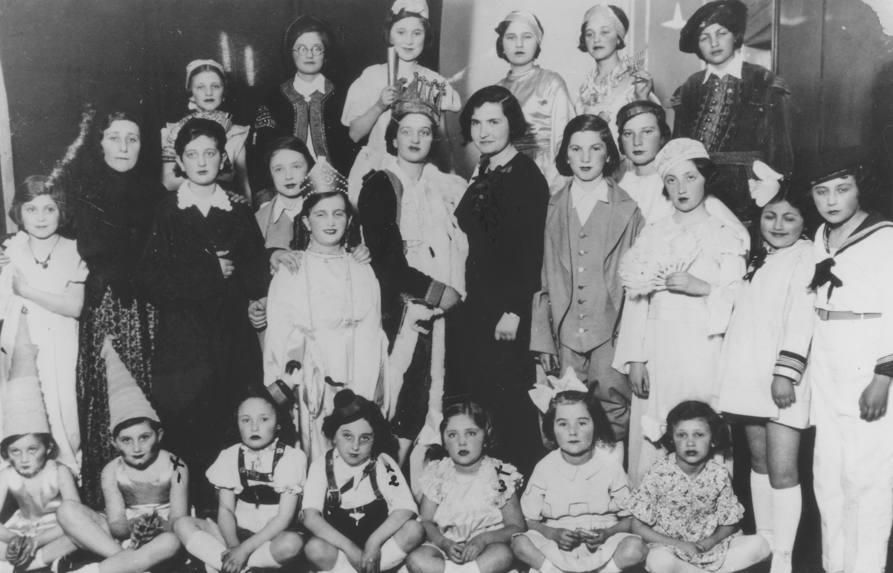 Group portrait of students at the Mukachevo Beit Yaakov school in their Purim costumes.  Those pictured include Erika Kestenbaum (front row, second from the left), Magda Meisels (front row, fourth from the left), Magda Kestenbaum (front row, third from the right), Suri Kasztner (second row, second from the right), Ibi Weiss (second row, far left), Eva Keleti, Judith Kestenbaum (second row, behind Magda Meisels) and Maca Stern (top row, left).
