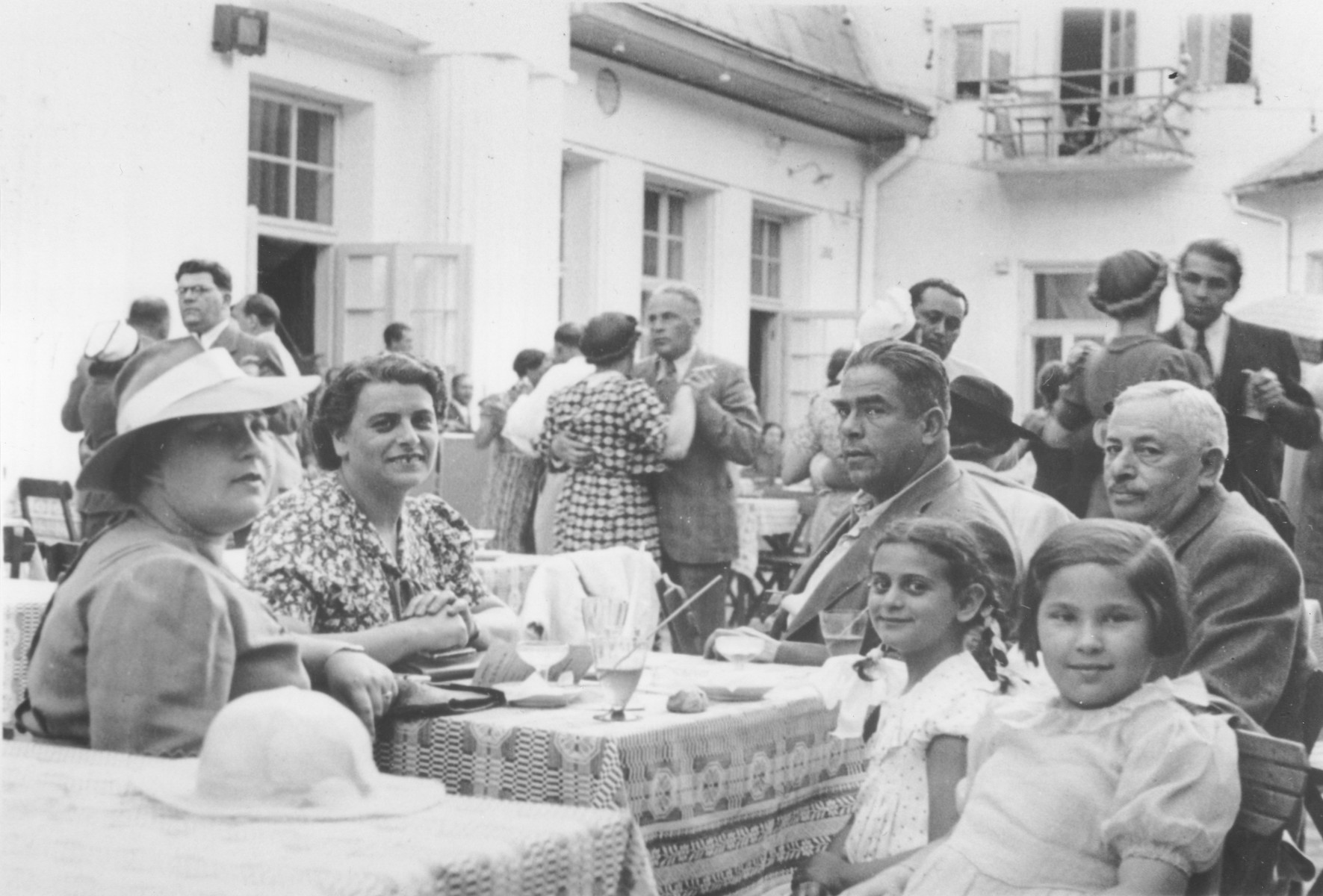 The Berkowicz family eats in an outdoor cafe with friends and relatives while on vacation in the resort town of Krynica,   Among those pictures are Bina Berkowicz (second from the left), Basia Berkowicz (second child from the right) and Wilek Taca (far right).